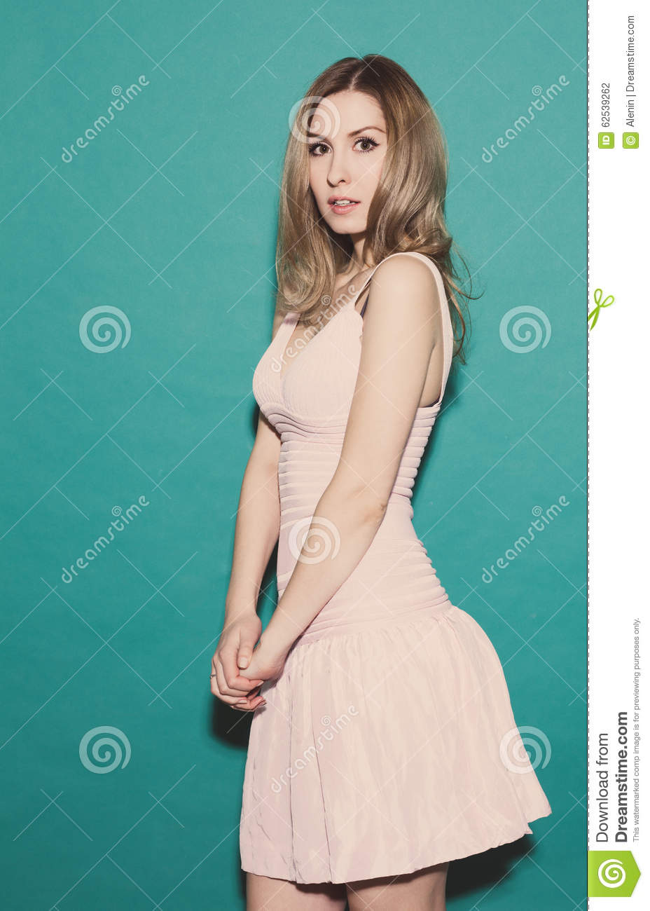 Frightened girl, standing in a short pink dress posing on a green background in the studio. Toned