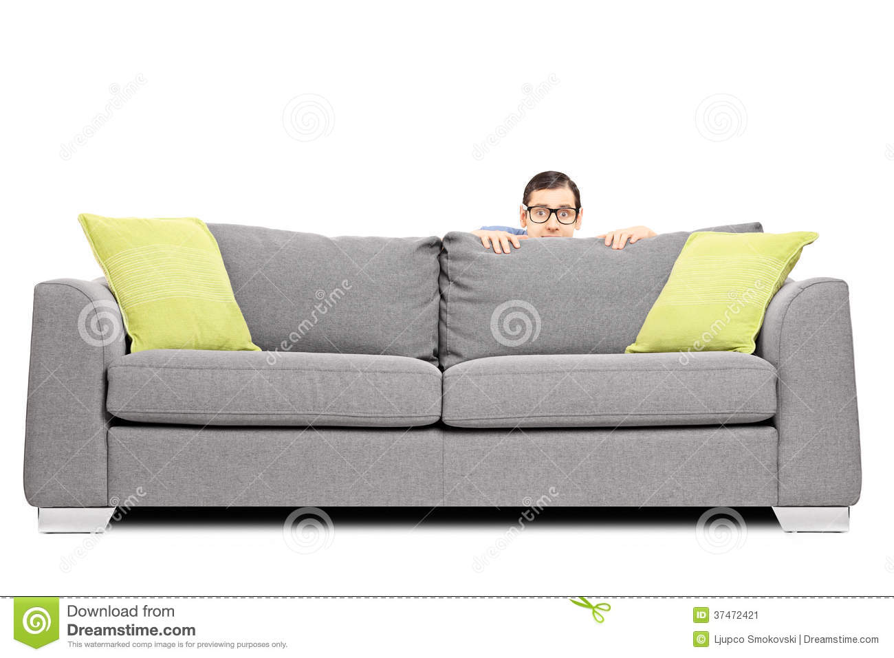 Frightened Man Hiding Behind A Sofa Stock Image