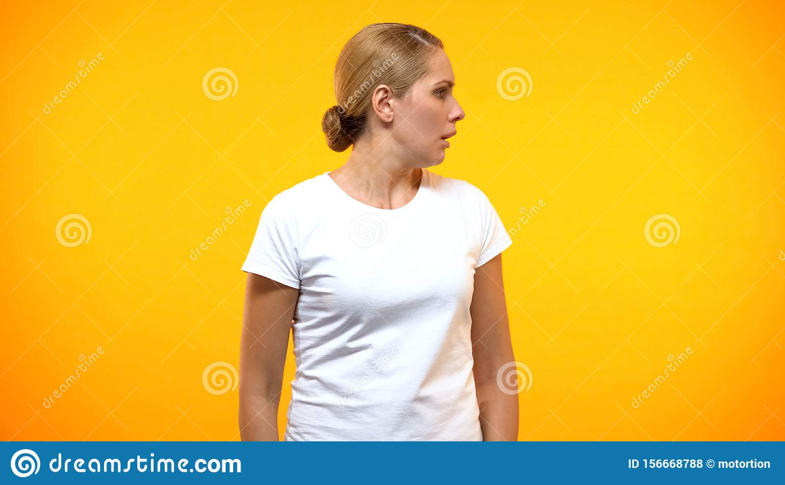 Frightened woman looking right on bright background, fear expression, anxiety