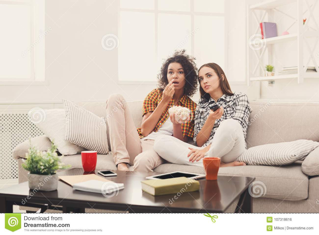 Groovy Frightened Young Women Watching Tv At Home Stock Photo Download Free Architecture Designs Scobabritishbridgeorg