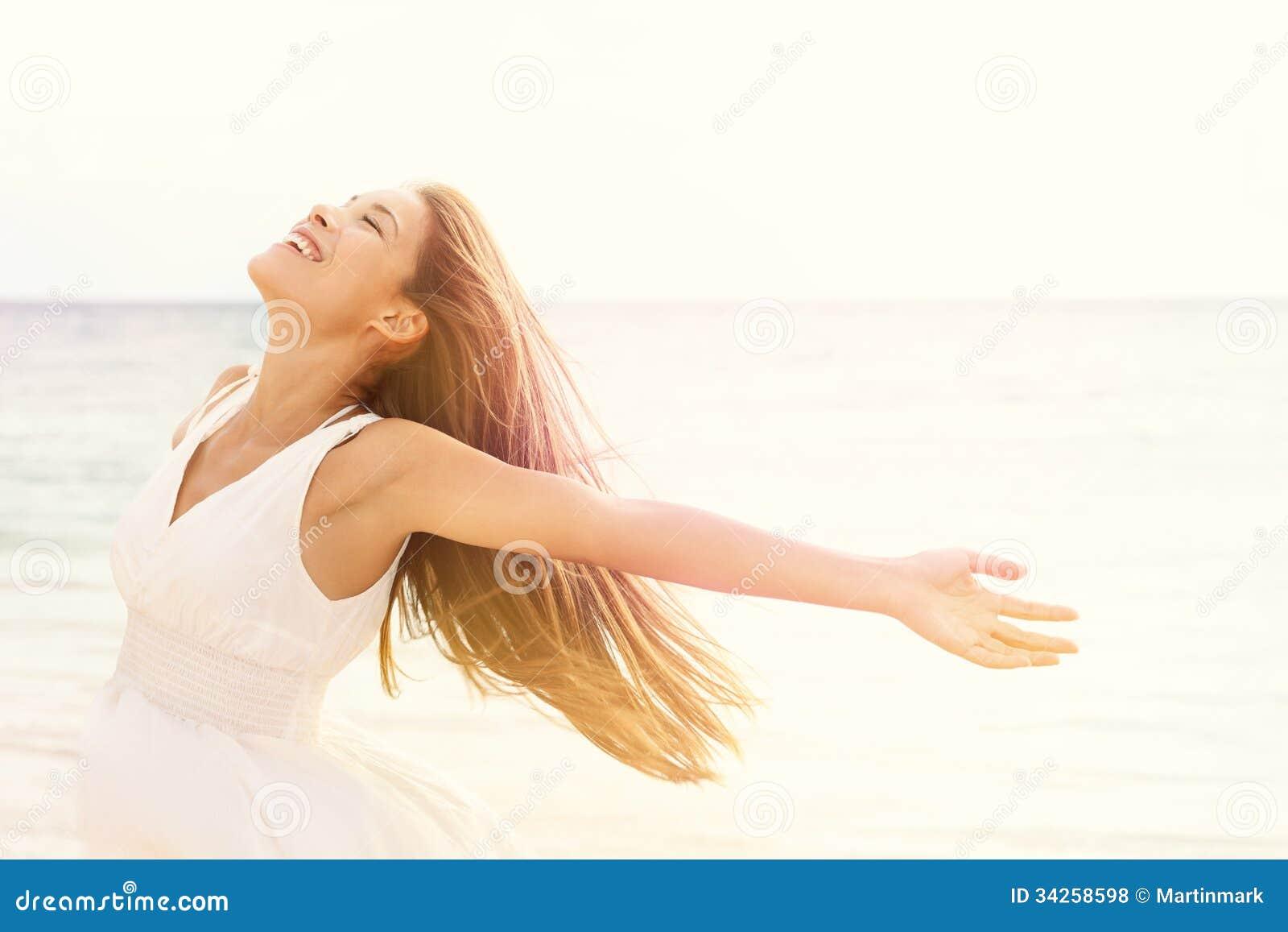 Frihetskvinna i fri lyckasalighet på stranden
