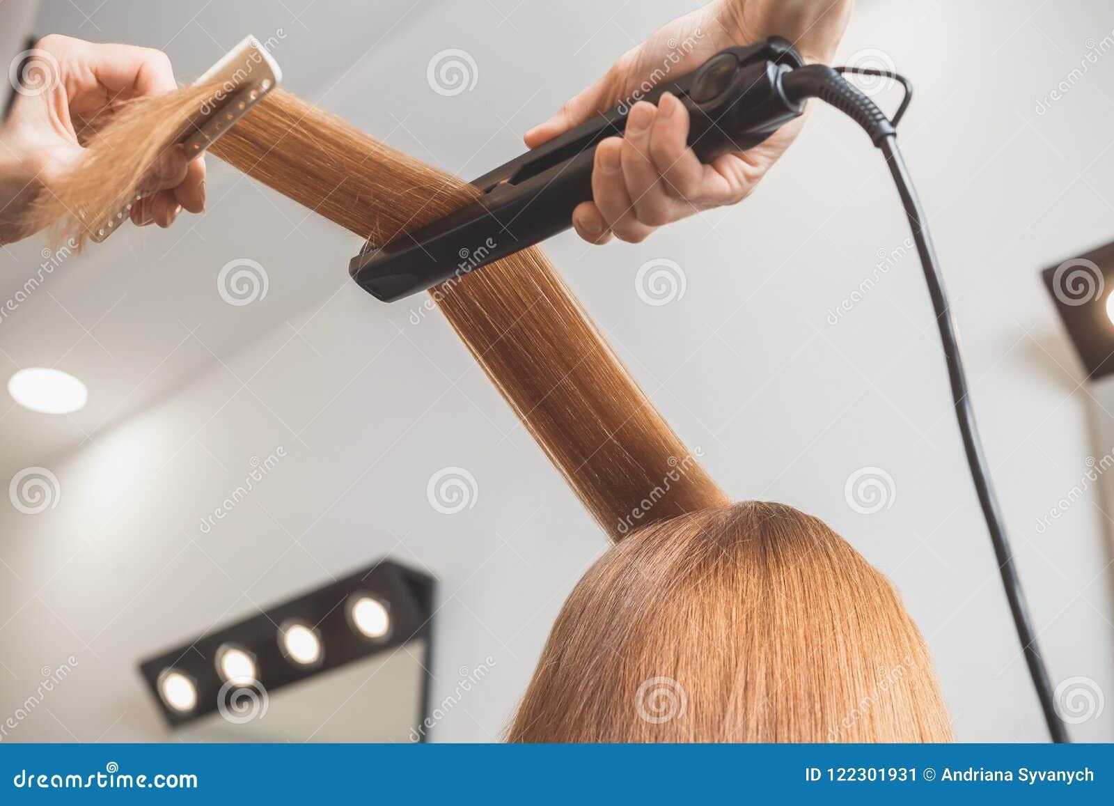 Frisör som gör en frisyr för klient