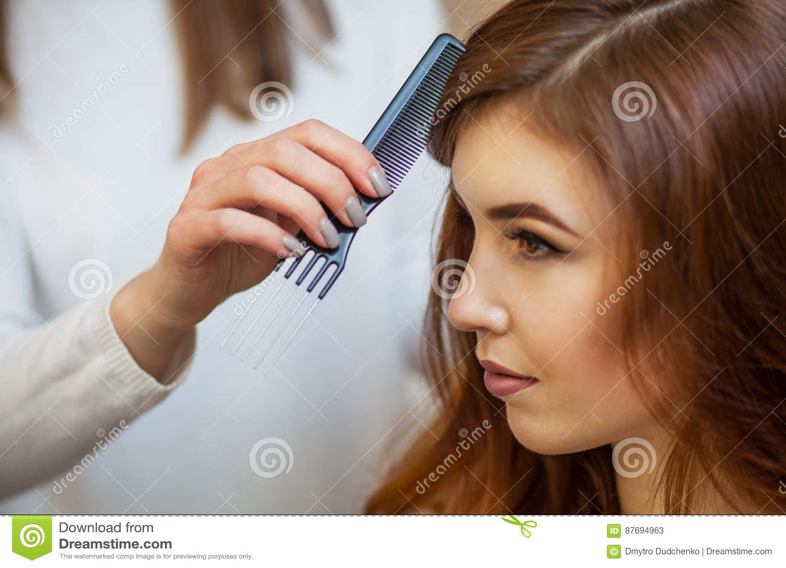 Frisör som kammar hennes långa röda hår av hans klient i skönhetsalongen