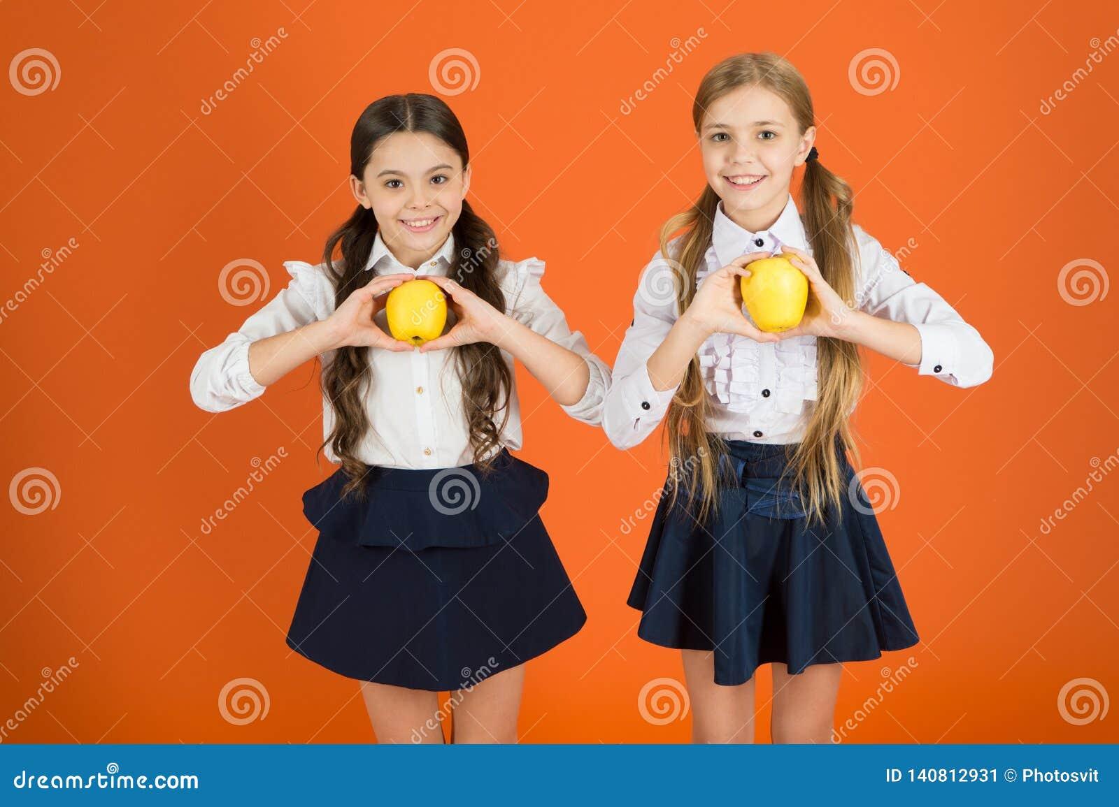 Frisch und geschmackvoll Kleine Mädchen, die natürliche Vitaminnahrung essen Nette Schulmädchen, die Äpfel halten Schulkinder mit