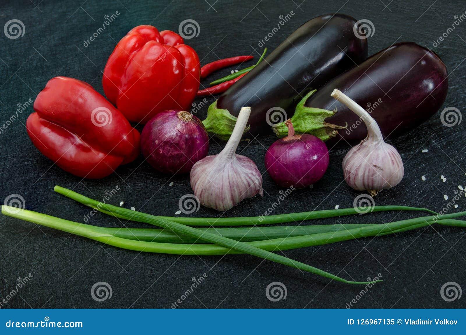 Frische Auberginen, Pfeffer, Knoblauch, Zwiebel auf schwarzem Hintergrund