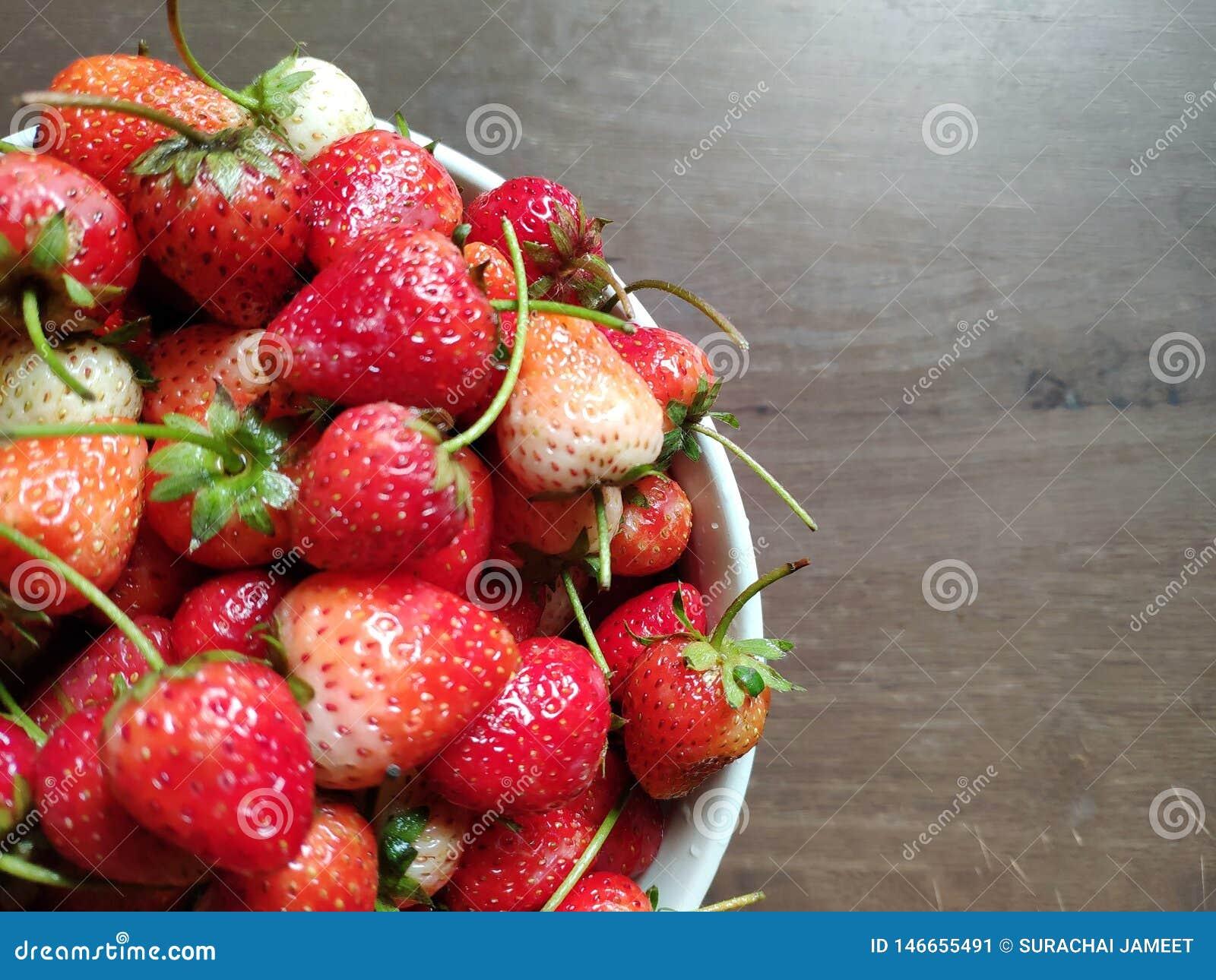 Frische Erdbeeren sind in der weißen Schüssel auf Holztisch