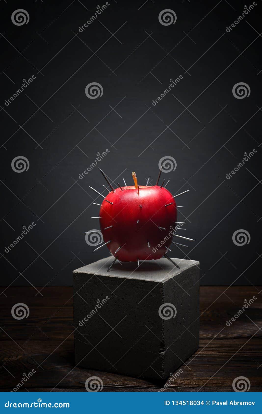 Frische Frucht auf dunklem Hintergrund auf konkretem Stand Saftiges rotes Apple mit den scharfen Dornen