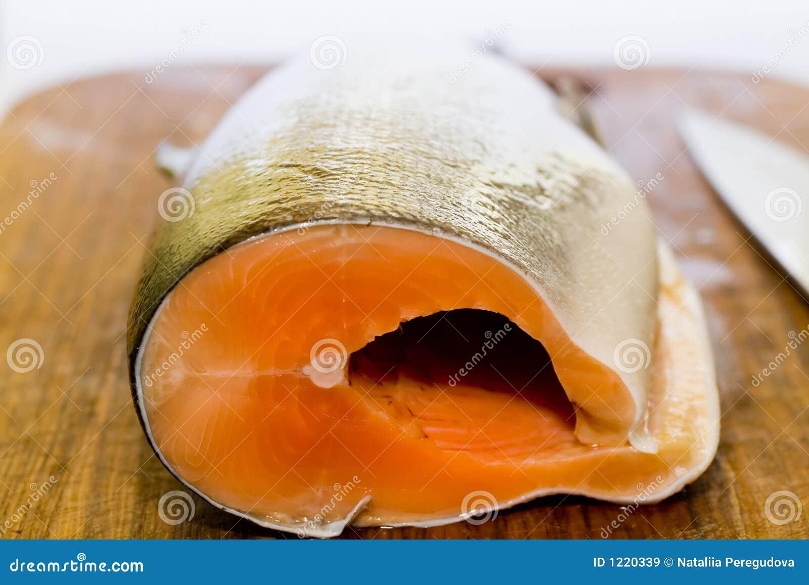 Frische Lachsfische mit Messer auf hölzernem kochendem Schreibtisch