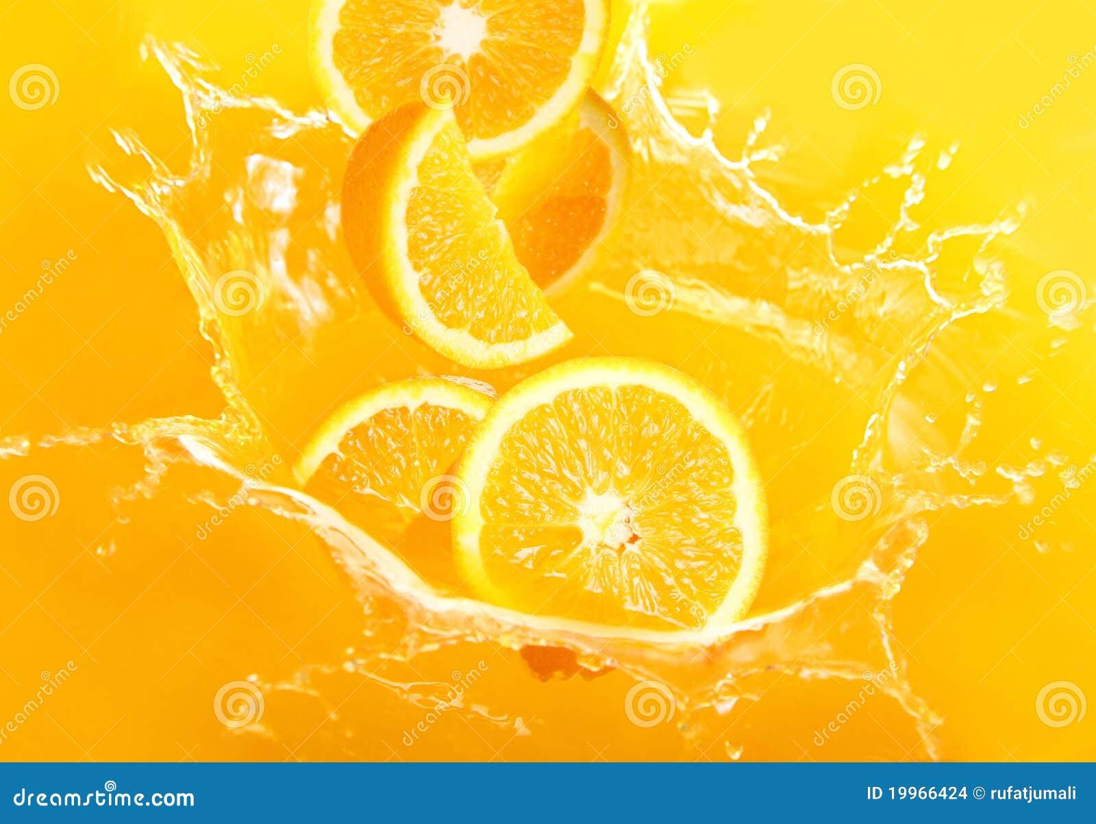 Frische Orangen, die in Saft fallen