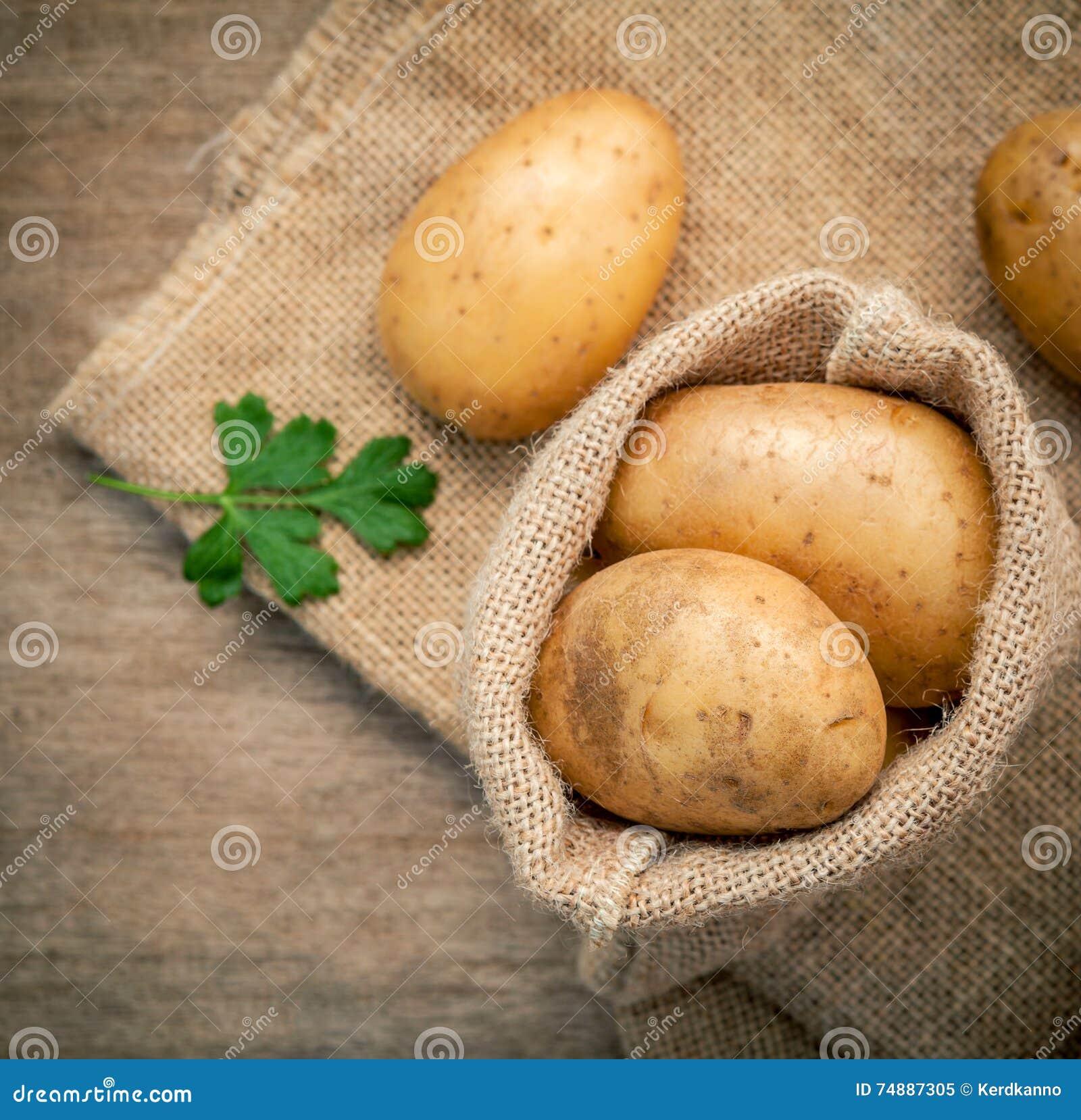 Frische organische Kartoffeln der Nahaufnahme im Hanfgrund bauschen sich mit Petersilie an