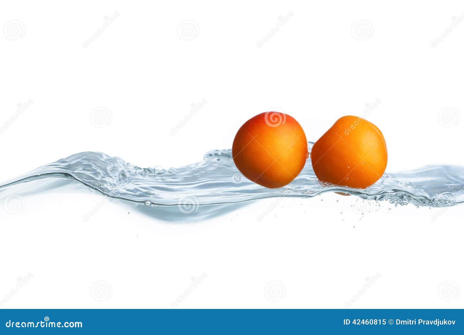 Frische reife Aprikose fiel in Wasserspritzen