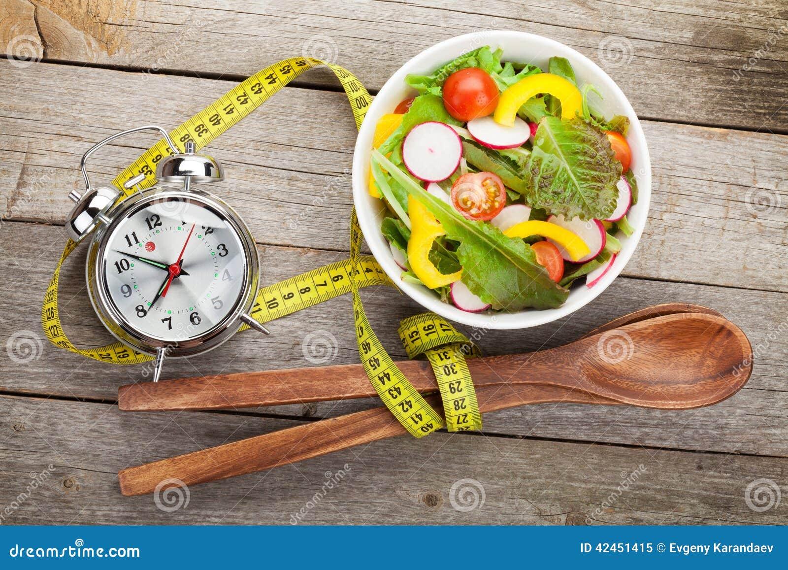 Frischer gesunder Salat und messendes Band auf Holztisch