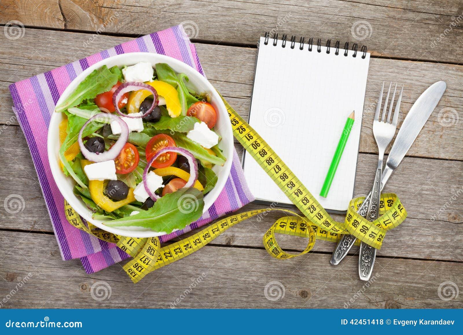 Frischer gesunder Salat und Notizblock für Kopienraum