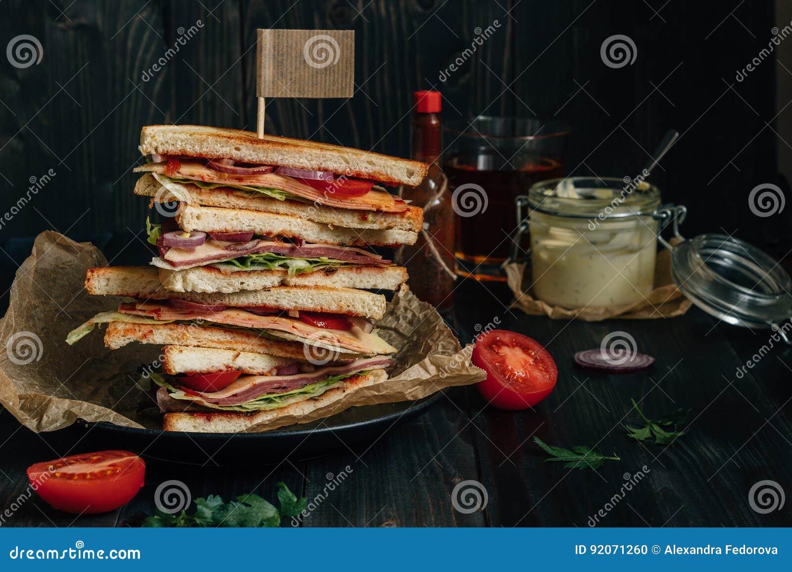Frisches geschmackvolles Club Sandwich und Soßen auf der hölzernen dunklen Tabelle