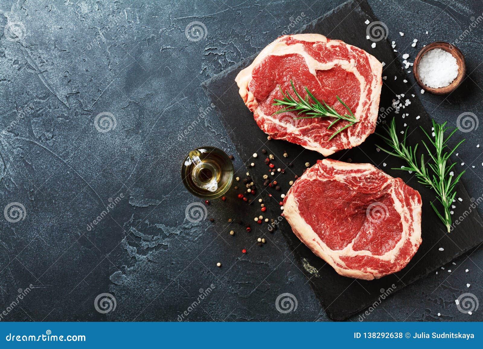 Frischfleisch auf Draufsicht des Schieferschwarzbrettes Rohes Rindfleischsteak und -gewürze für das Kochen
