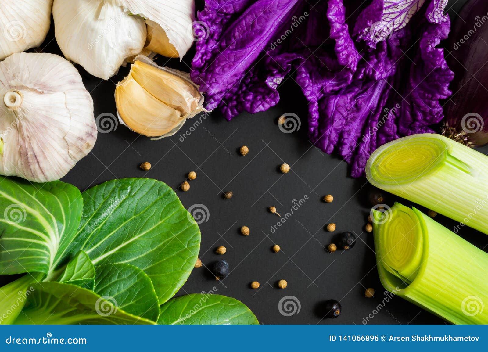 Frischgemüse: bok choy Chinakohl, Knoblauch, Porree und Salat auf schwarzem Hintergrund Gesunde Nahrung Flach-Lage, Draufsicht