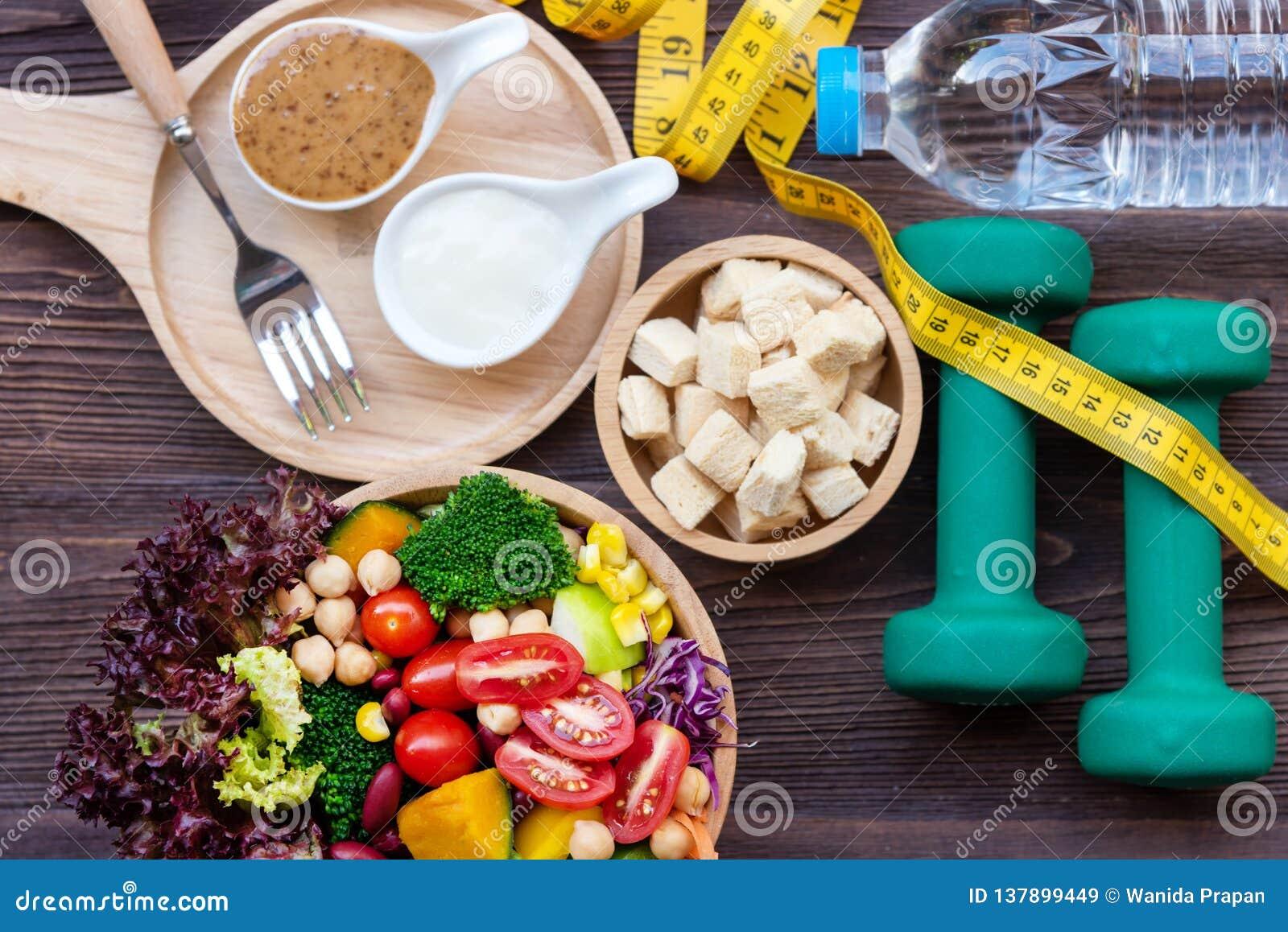 Frischgemüsesalat und gesunde Nahrung für Sportausrüstung für Frauen nähren das Abnehmen mit Maßhahn für Gewichtsverlust auf hölz