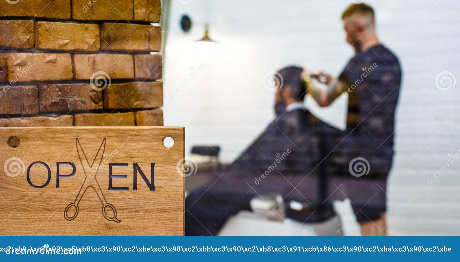 Frisersalongsalong Öppen barder shoppar Frisör eller barberare Mannen som besöker frisören i barberare, shoppar Man med skägget i