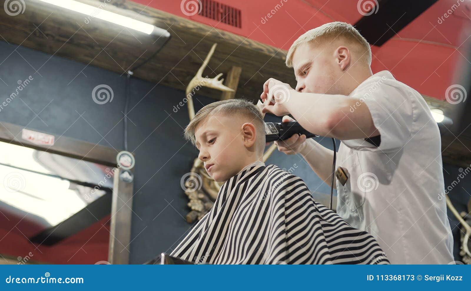Weihnachtsgeschenke Für Kunden Friseur.Friseur Mit Kundenkind Im Friseursalon Friseur Der Trimmer Und Kamm Im Friseursalon Verwendet Nettes Kind Das Auf Sitzt