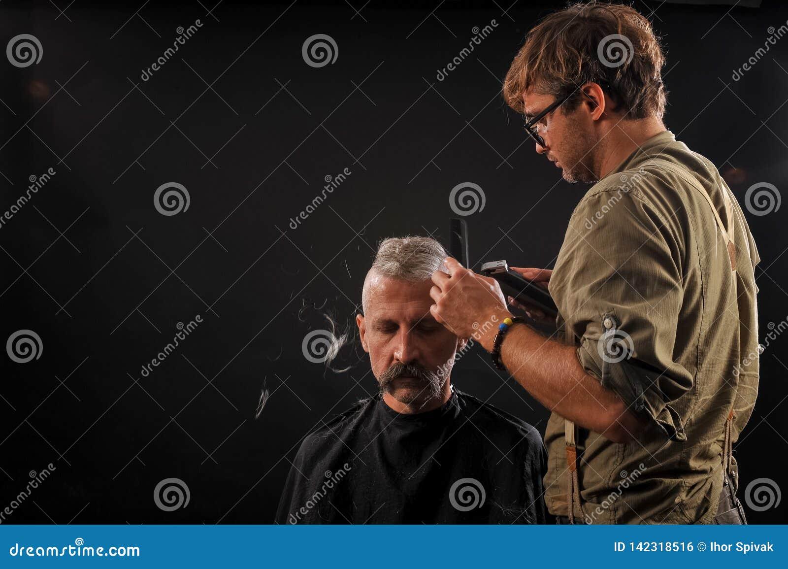 Friseur schneidet älteren Bürger mit einem Bart auf einem dunklen Hintergrund