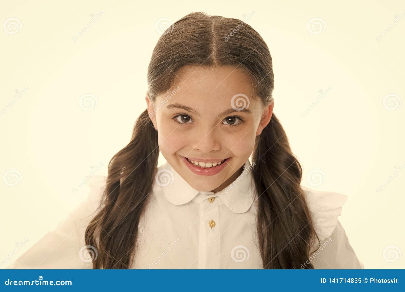Friseursalonservices für kleines Mädchen Kleines Mädchen, das mit dem langen Haar lokalisiert auf Weiß lächelt Glückliches Kind m