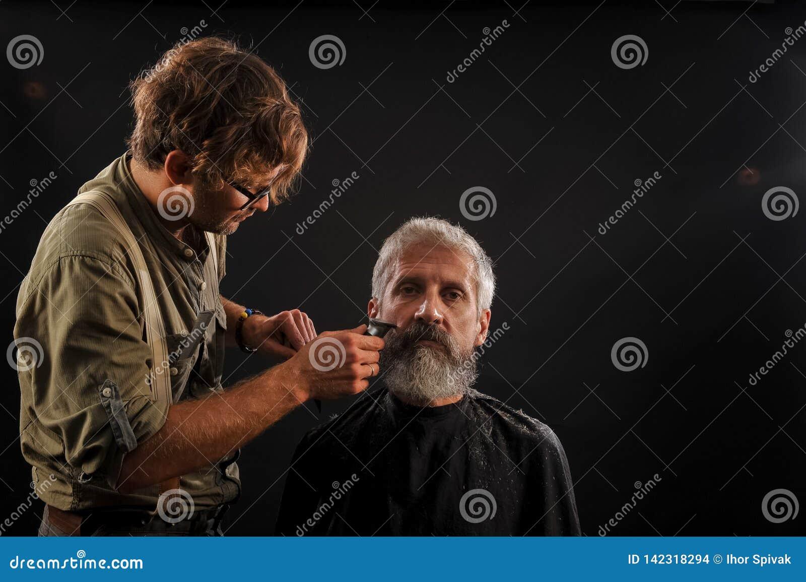 Friseurschnitte ein Bart zu einem Kunden zu einem älteren grauhaarigen Mann