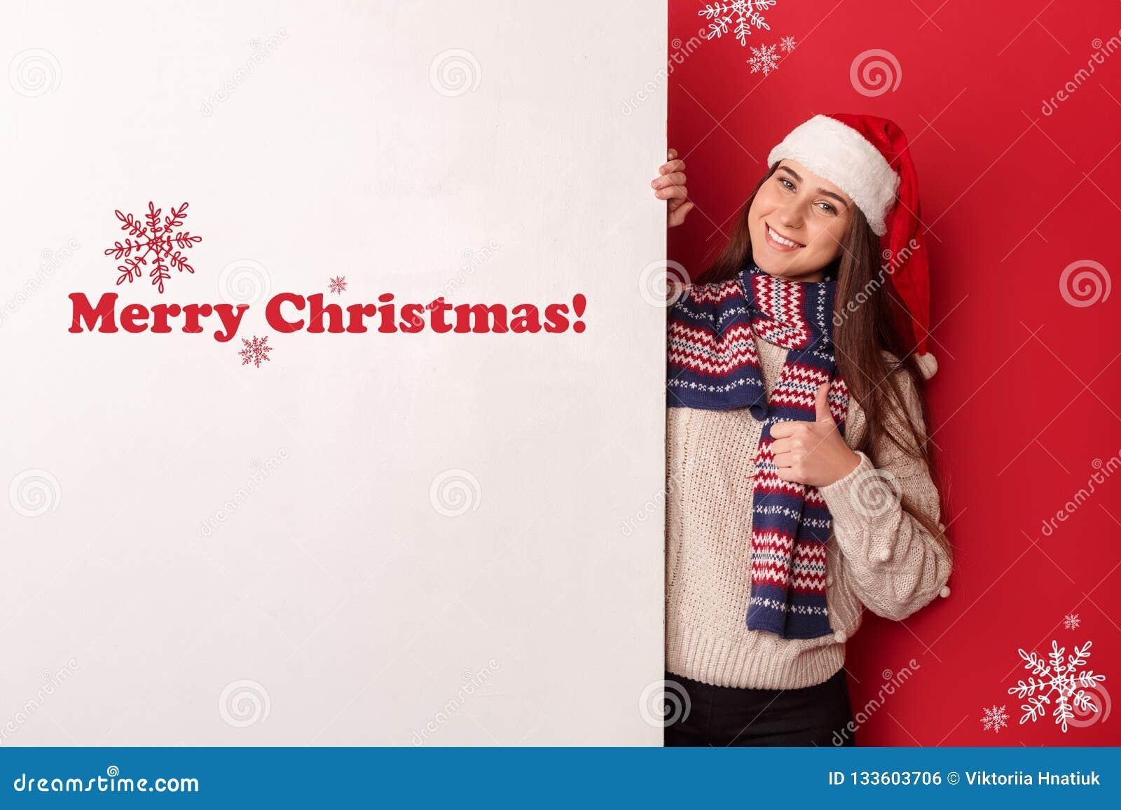 Fristil Bärande halsduk- och santa hattanseende för ung kvinna som isoleras på rött med tummen för vitt bräde upp att se kameran