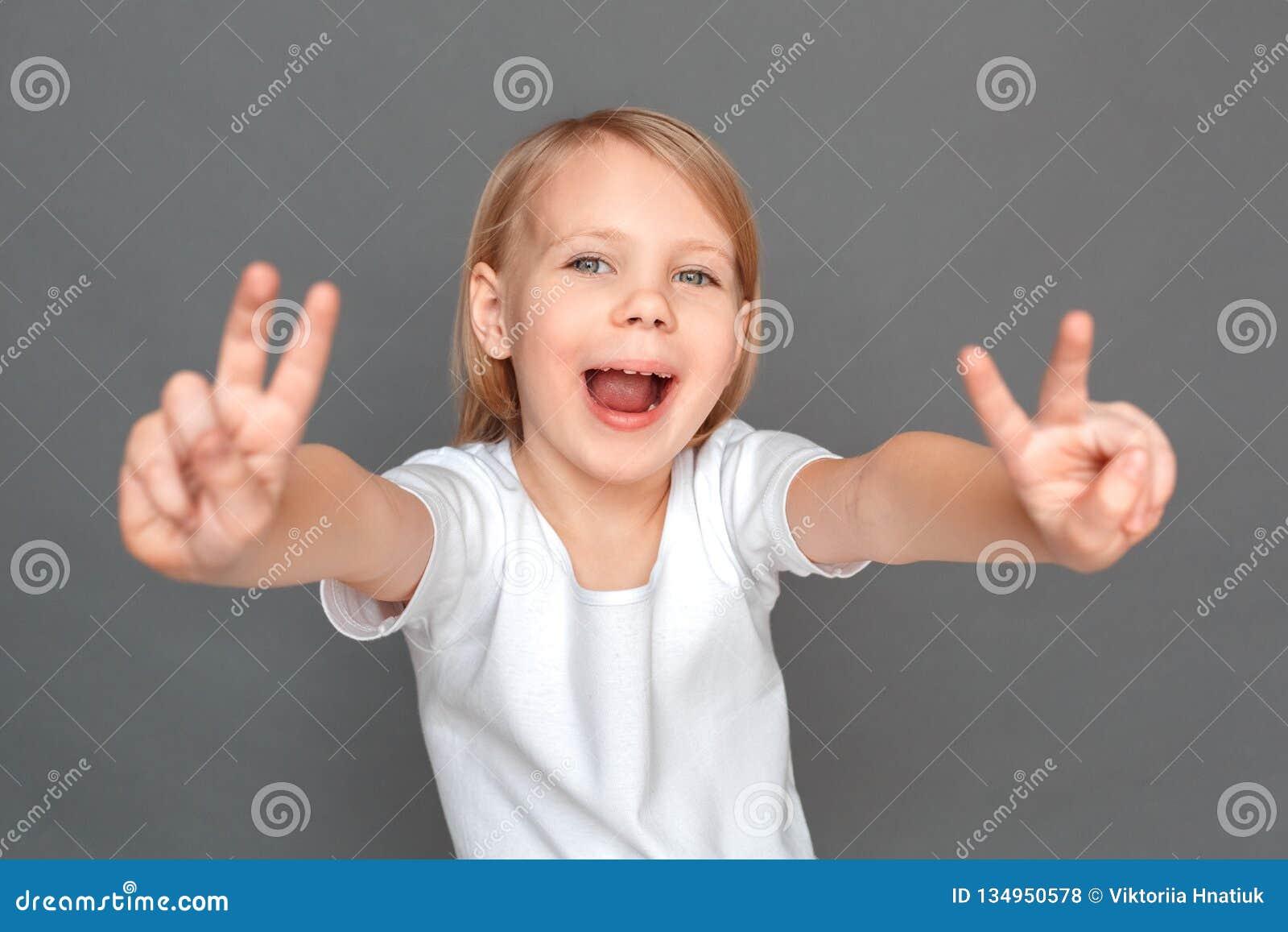 Fristil Lilla flickan på gråa visande horn gör en gest le skämtsam närbild