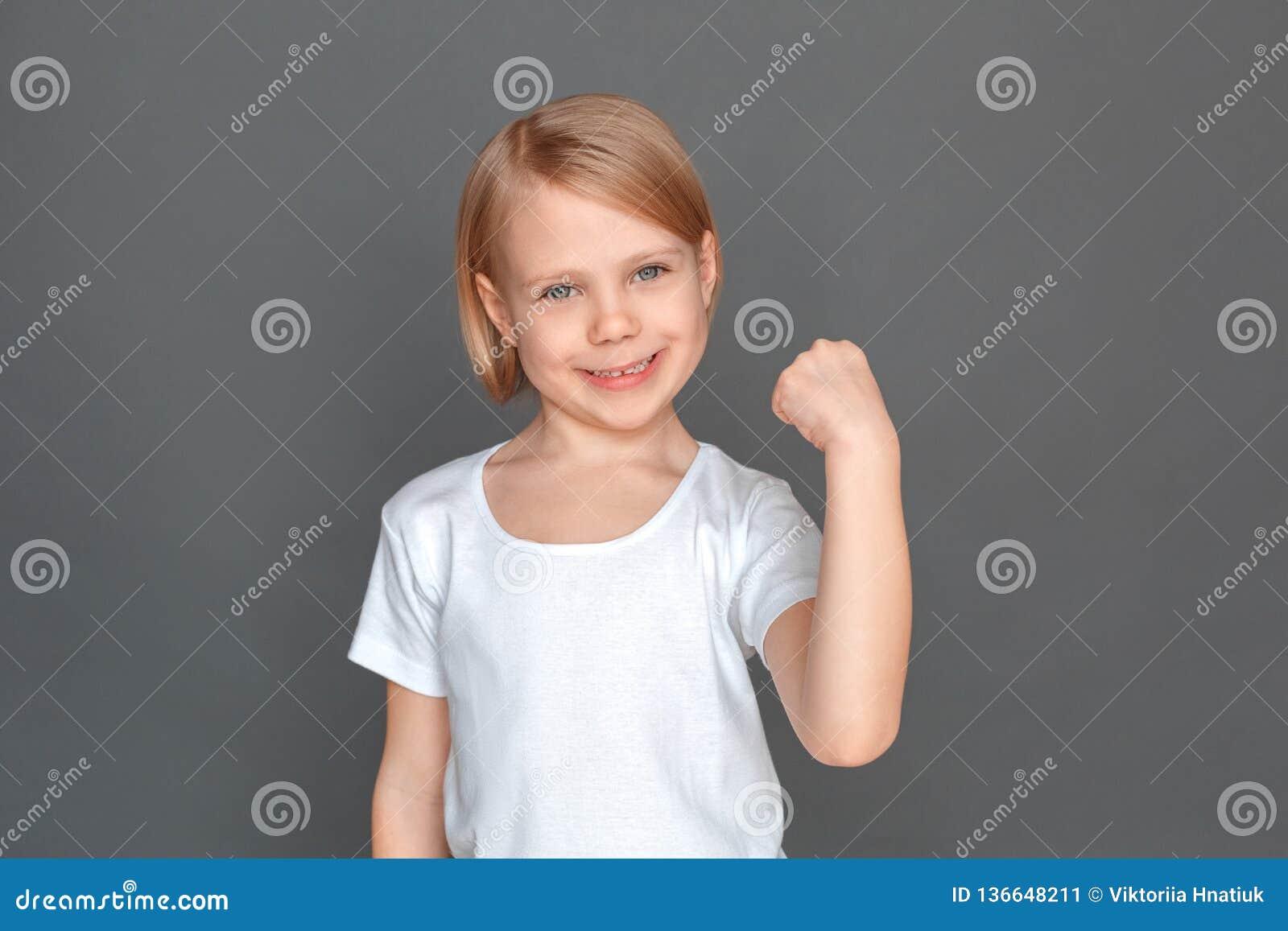 Fristil Liten flicka som isoleras på den gråa handen i näven som ler lyckad närbild