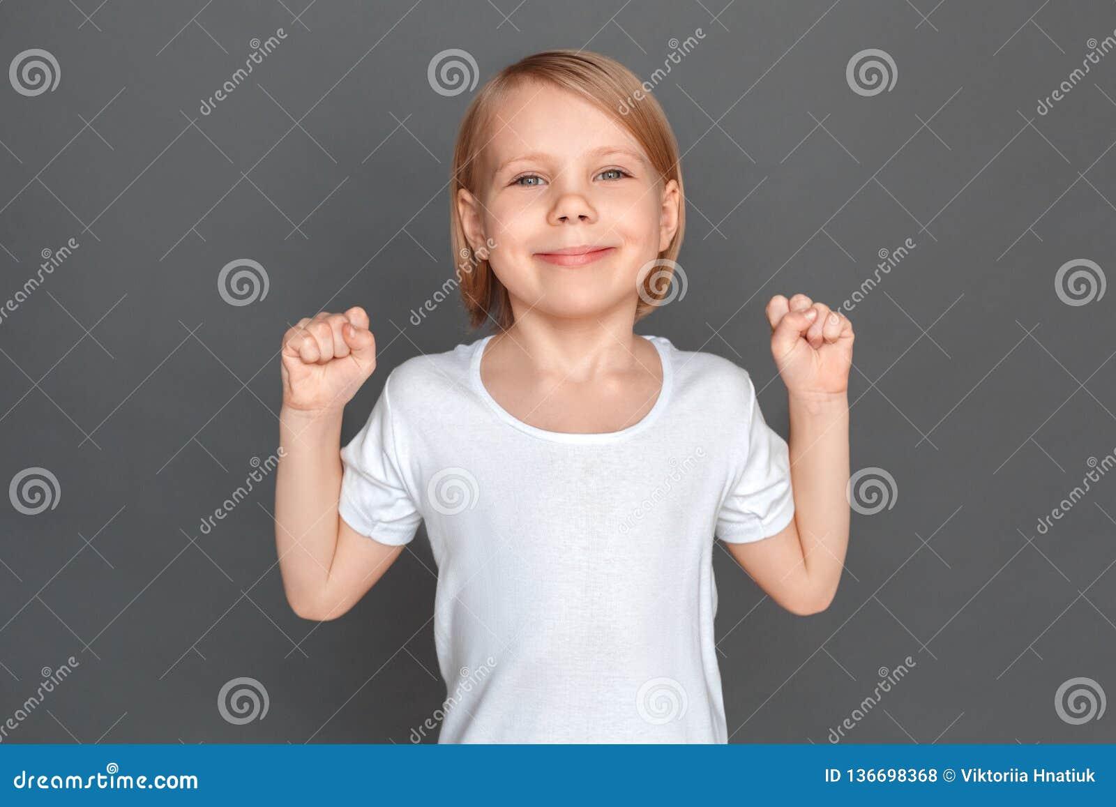 Fristil Liten flicka som isoleras på gråa händer i nävar som ler åt sidan lyckad närbild