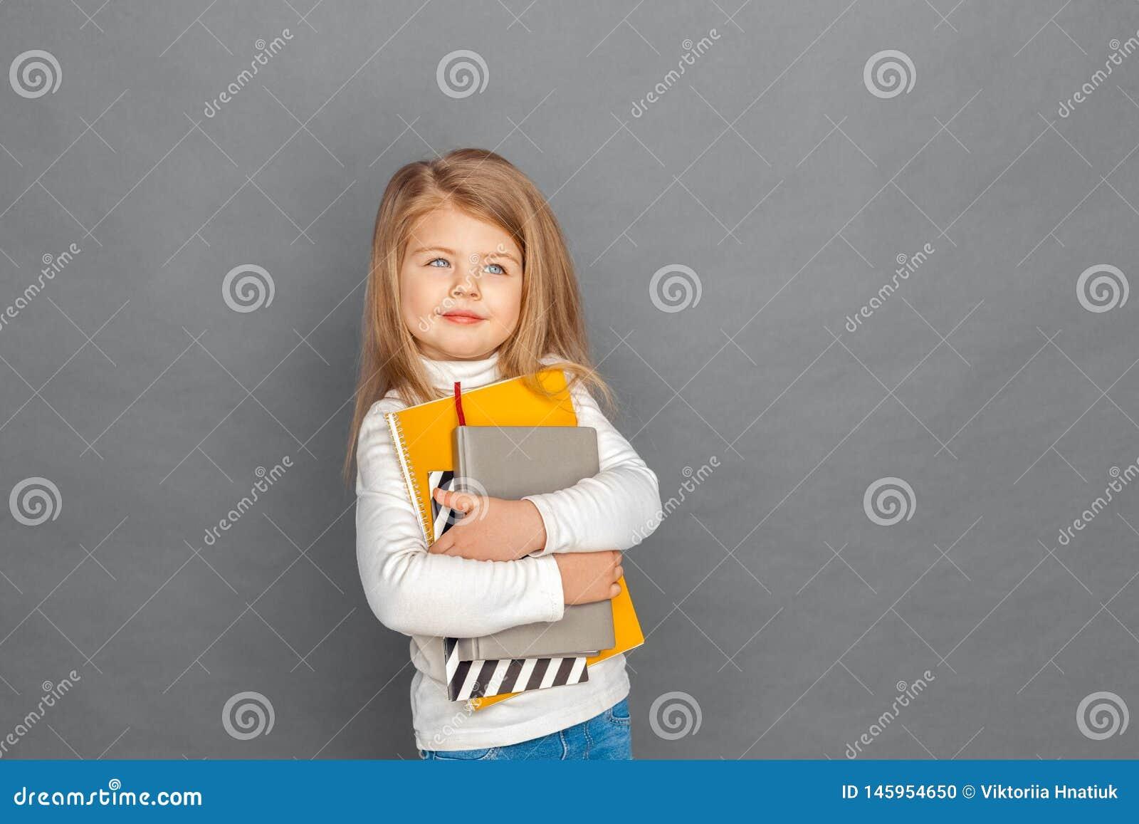 Fristil Liten flickaanseende som isoleras på grå färger med anteckningsböcker som ser åt sidan att le som är dreamful
