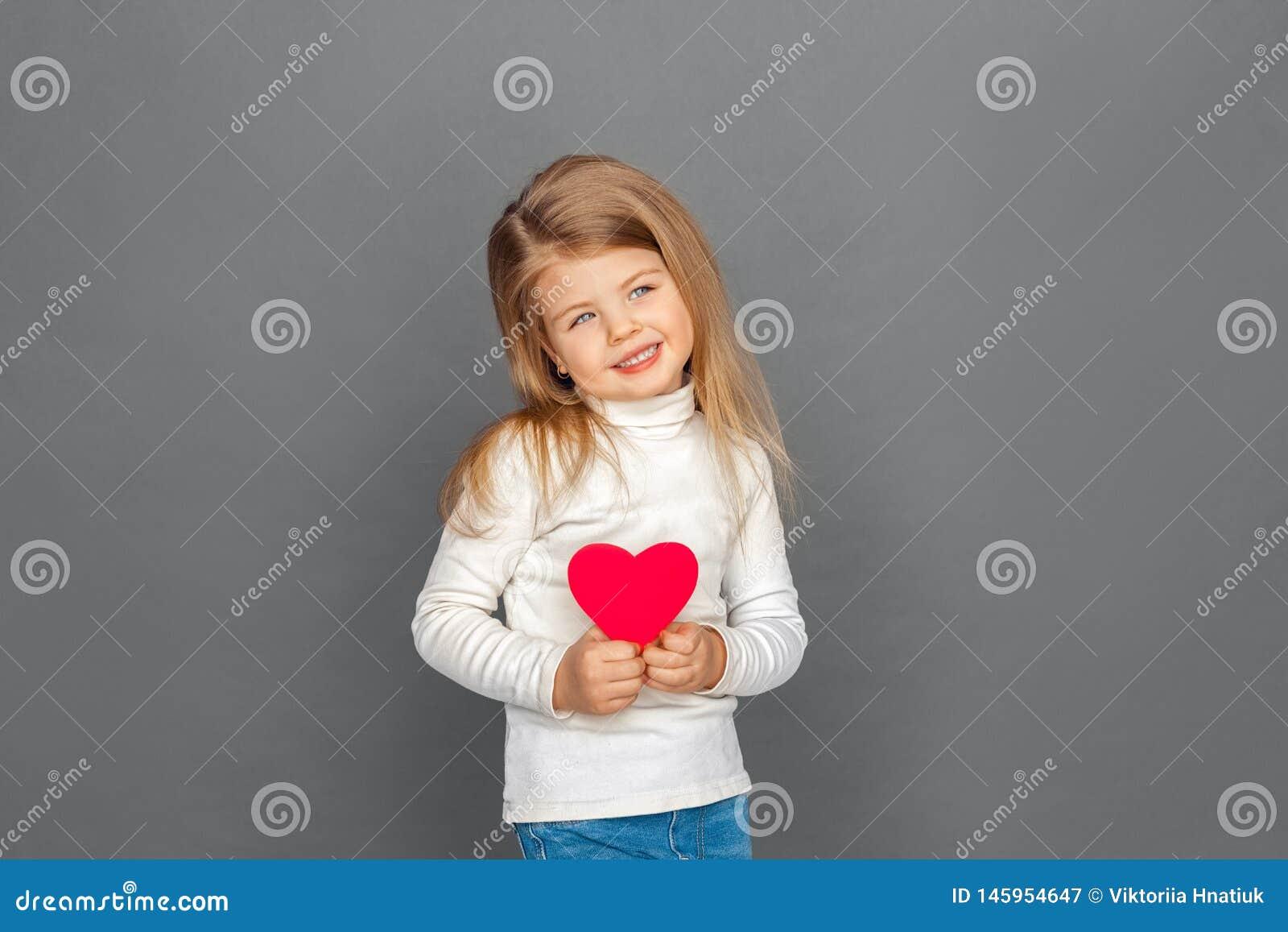 Fristil Liten flickaanseende som isoleras på grå färger med hjärtaformkortet som åt sidan ser gladlynt