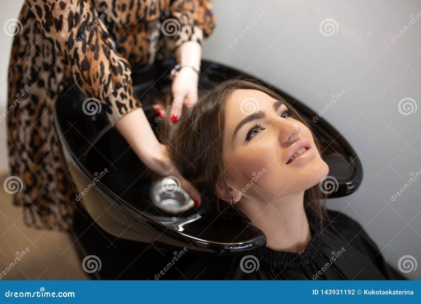 Frisyrförlagen tvättar hår av hennes klient hade
