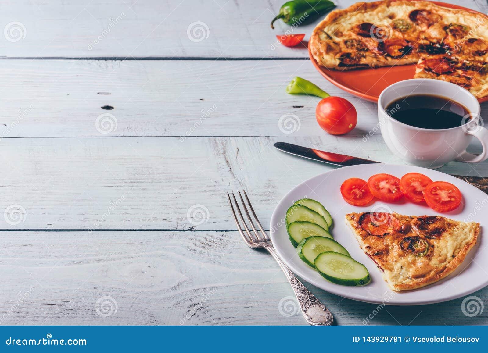 Frittata con chorizo, i pomodori ed il peperoncino rosso sul piatto e sul caffè