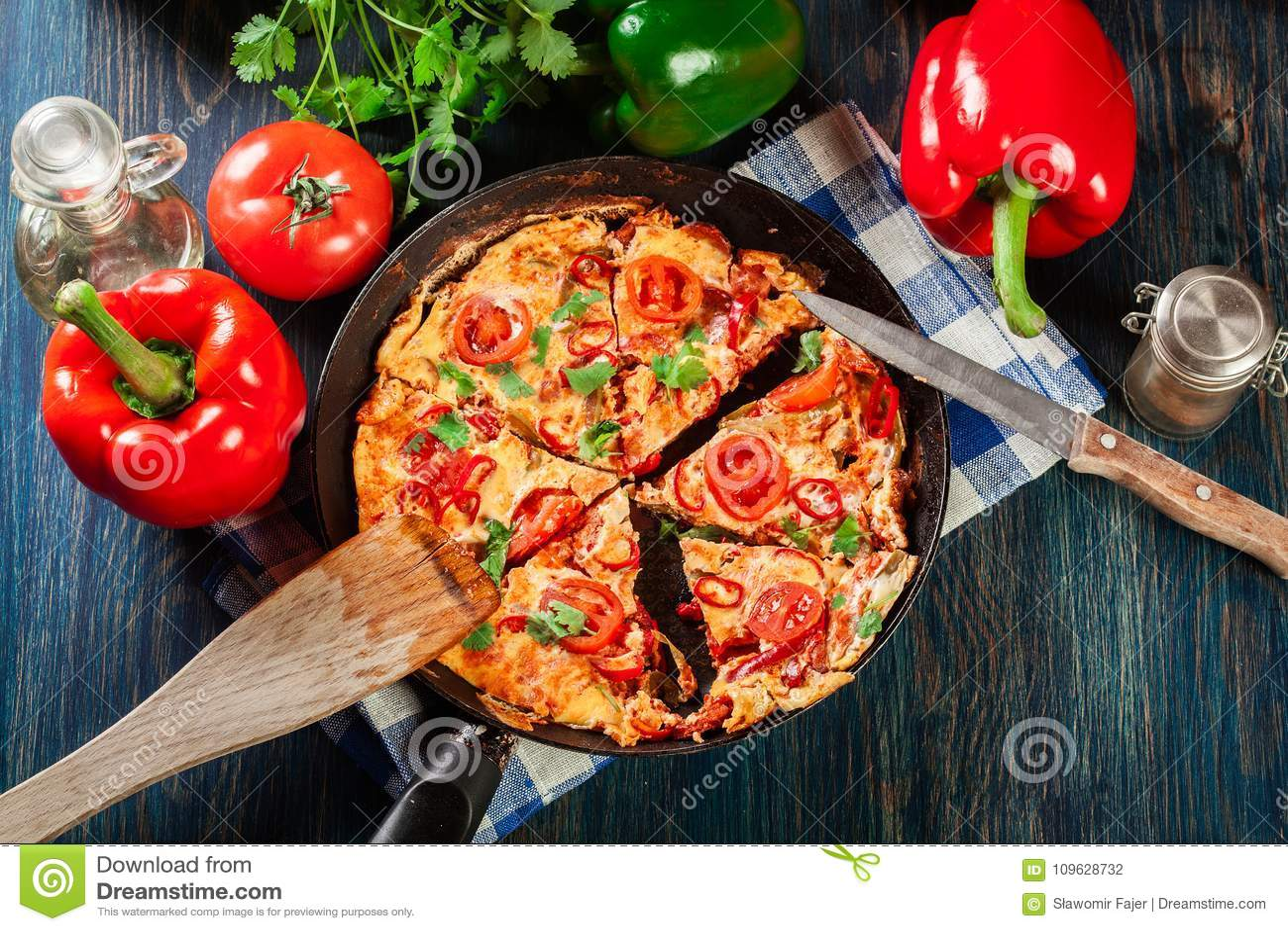 Frittata fait d oeufs, chorizo de saucisse, poivron rouge, poivron vert, tomates, fromage et piment dans une casserole sur la tab