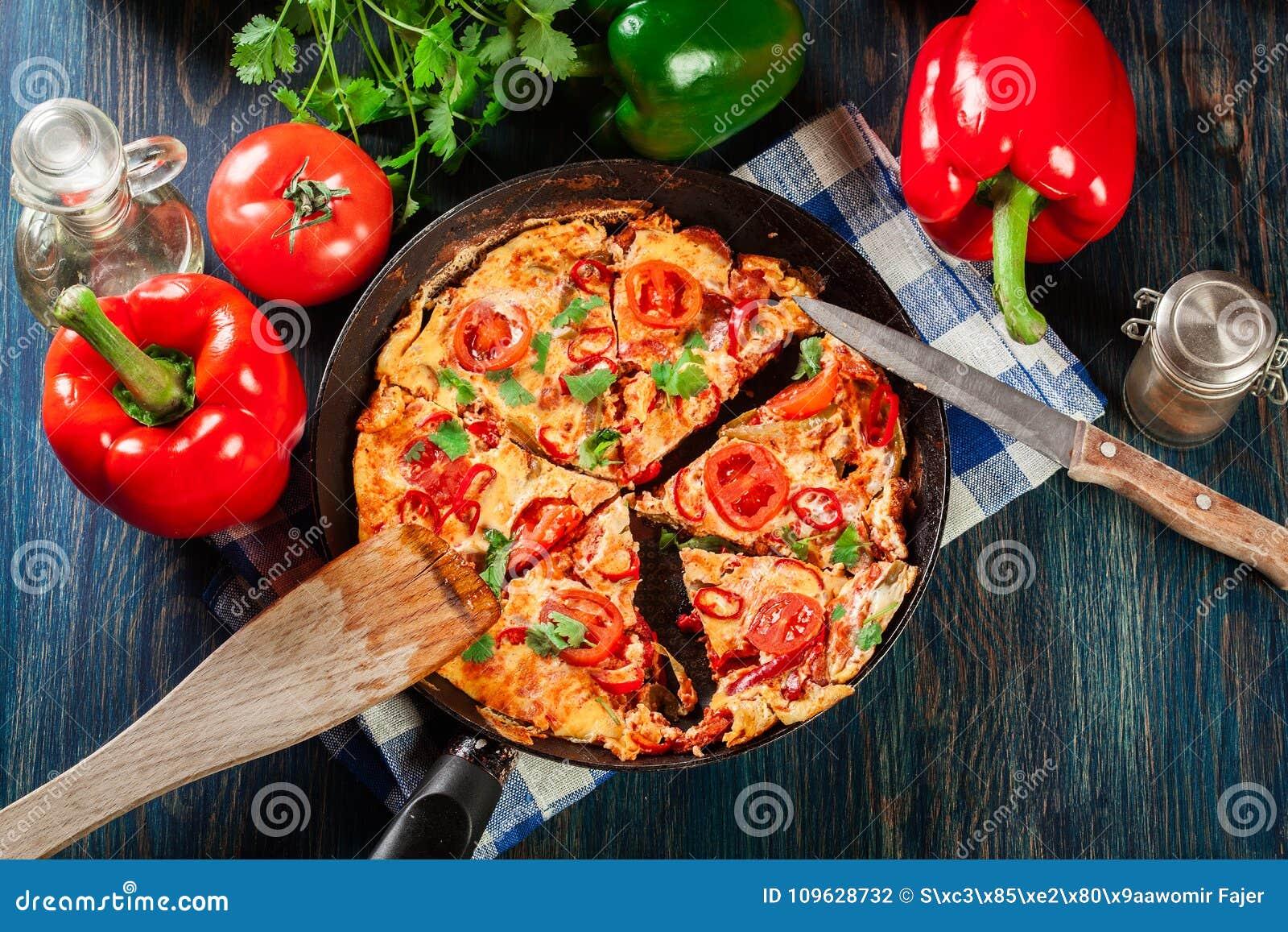 Frittata feito dos ovos, do chouriço da salsicha, da pimenta vermelha, da pimenta verde, dos tomates, do queijo e do pimentão em
