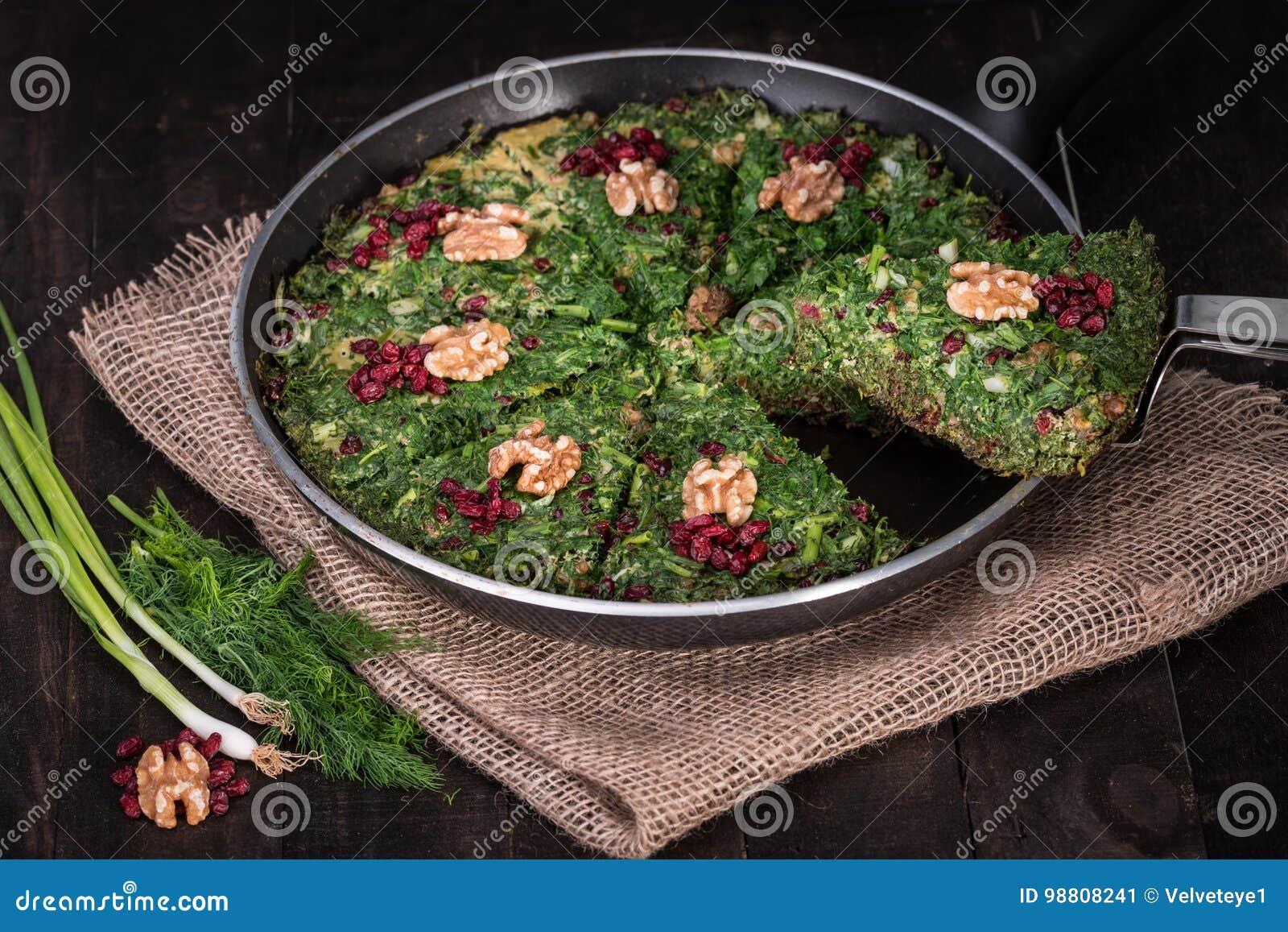 Frittata mezclado persa de las hierbas con el bérbero y la nuez en la cacerola Kuku y Zereshk