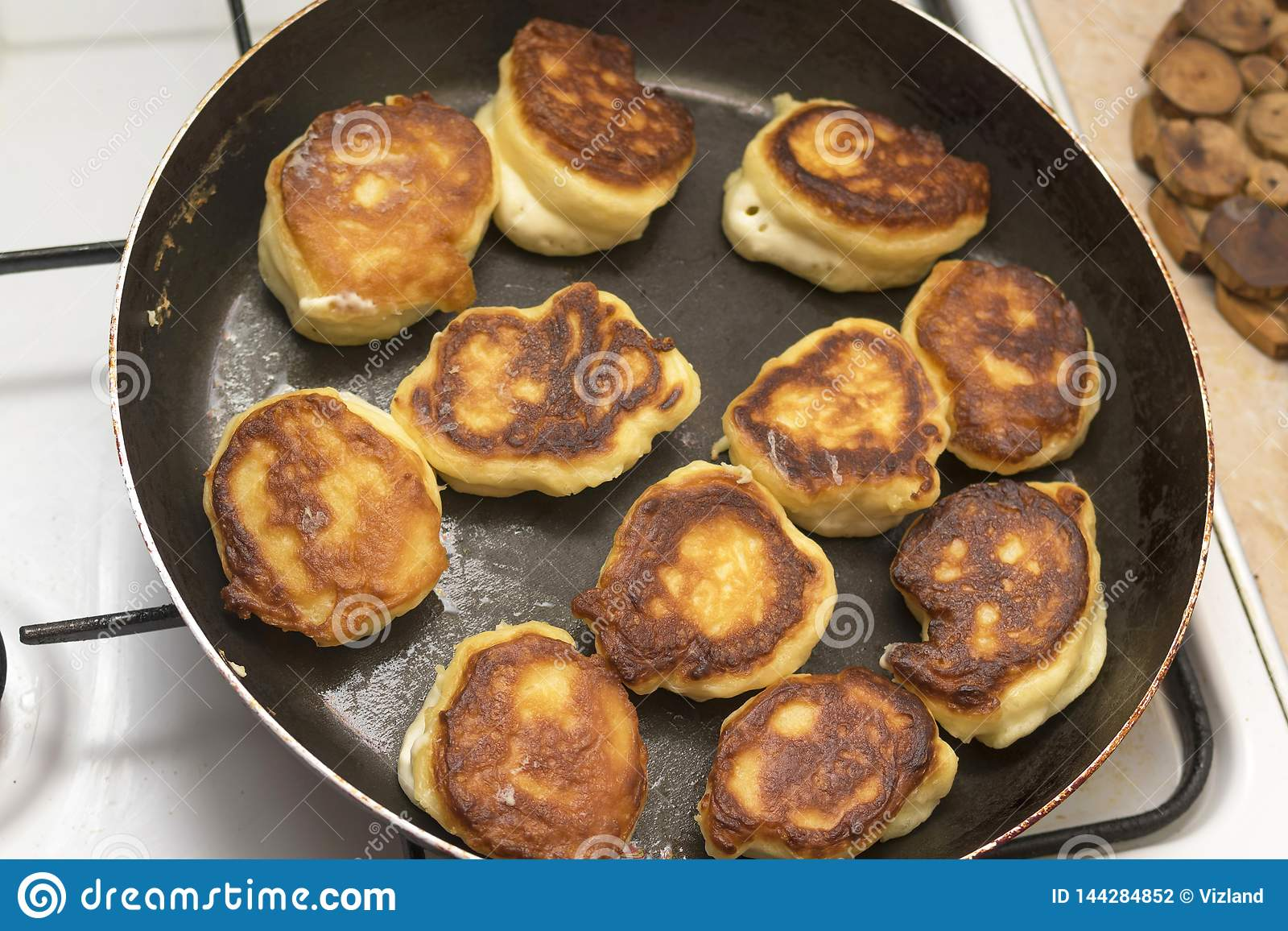 Fritters or dumplings are fried in a frying pan on vegetable oil, the top view