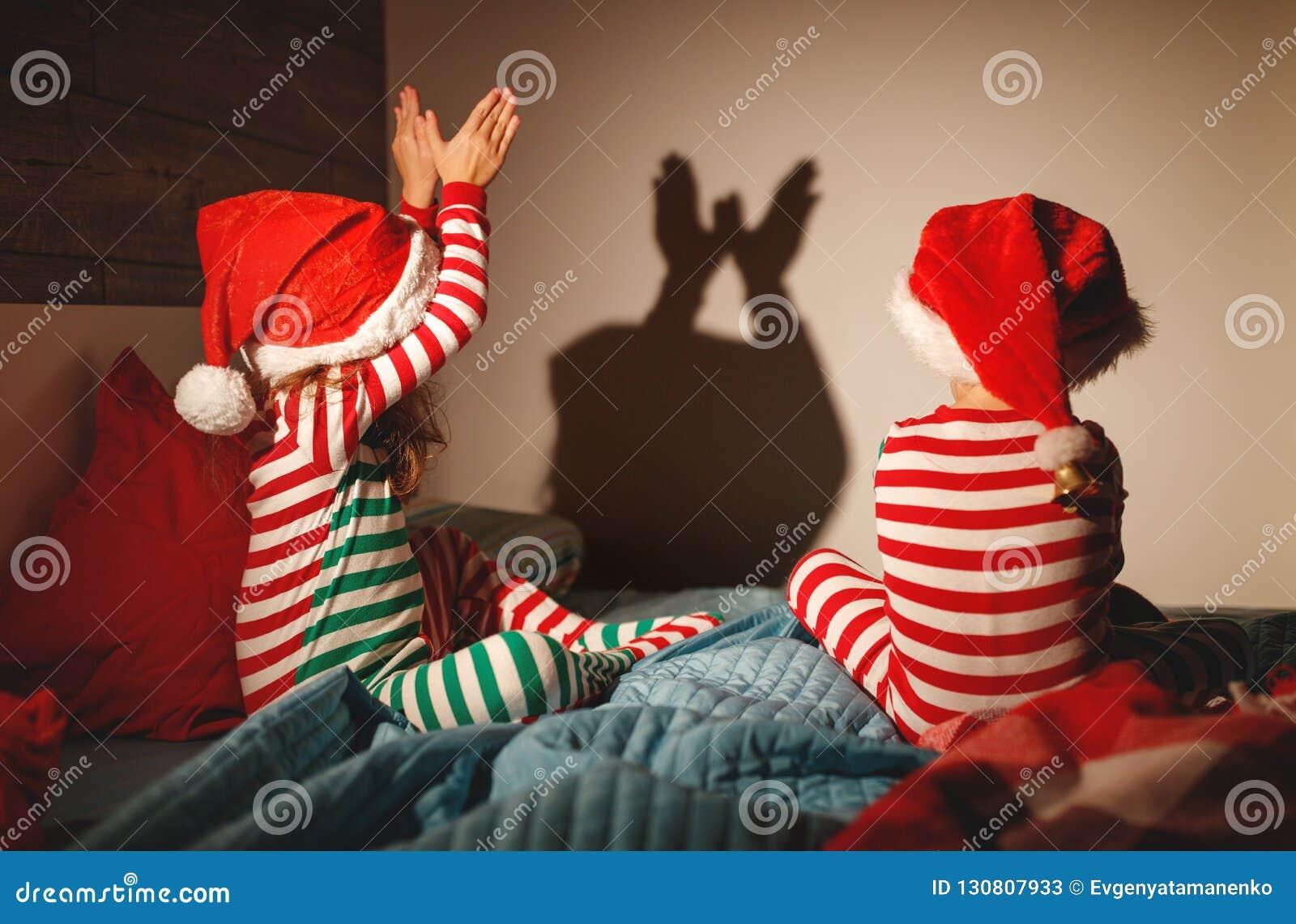 Frohe Weihnachten Kinder spielen Schattentheater im Bett