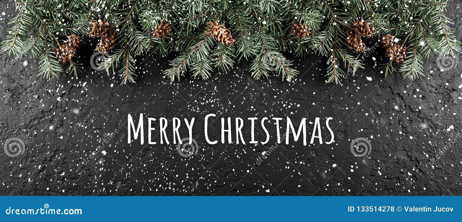 Frohe Weihnachten typografisch auf dunklem Feiertagshintergrund mit Rahmen von Tannenzweigen, Kiefernkegel
