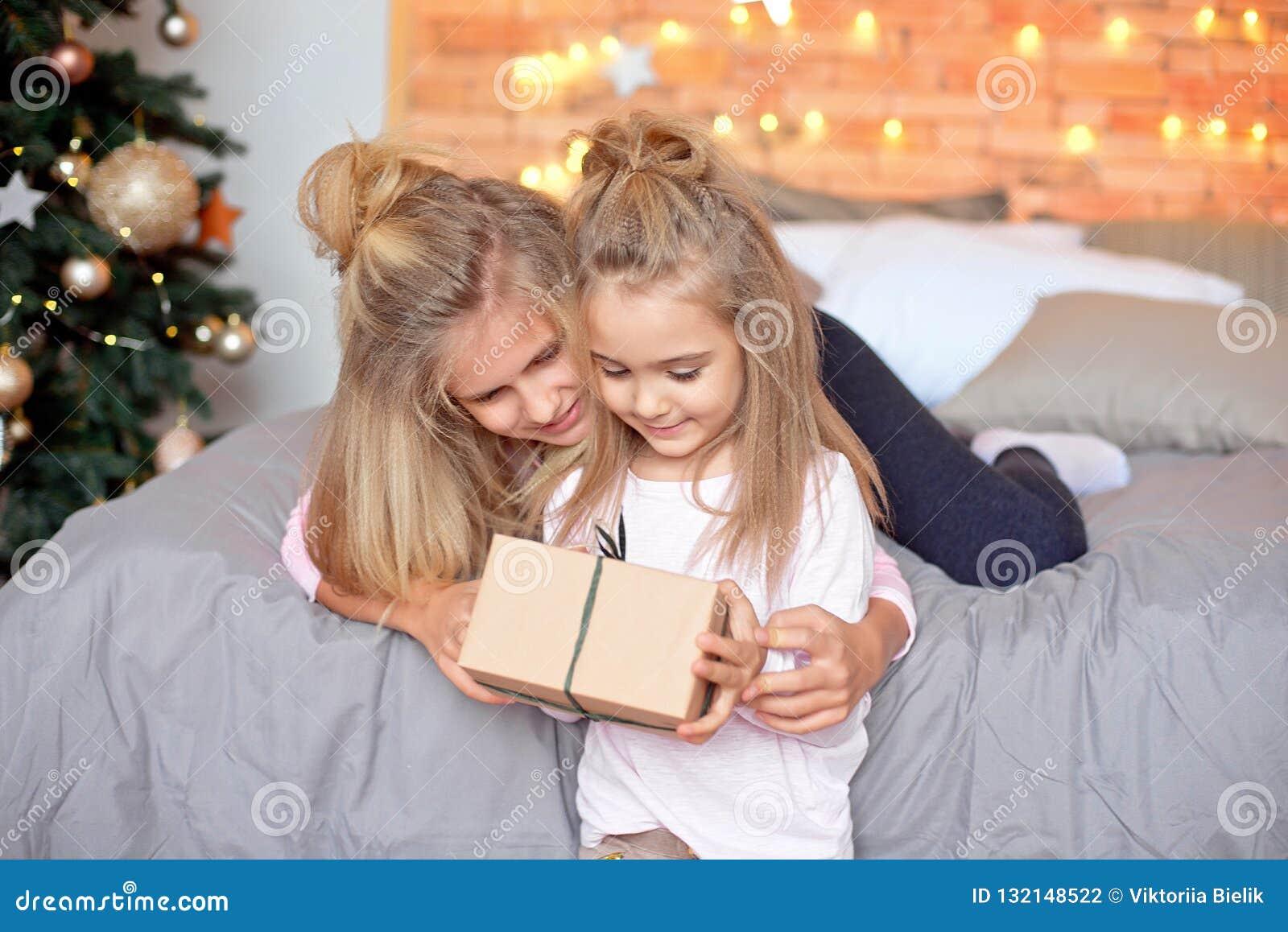 Frohe Weihnachten und frohe Feiertage Nette nette Kinder, die Geschenke öffnen Kinder, die Spaß nahe Baum morgens haben