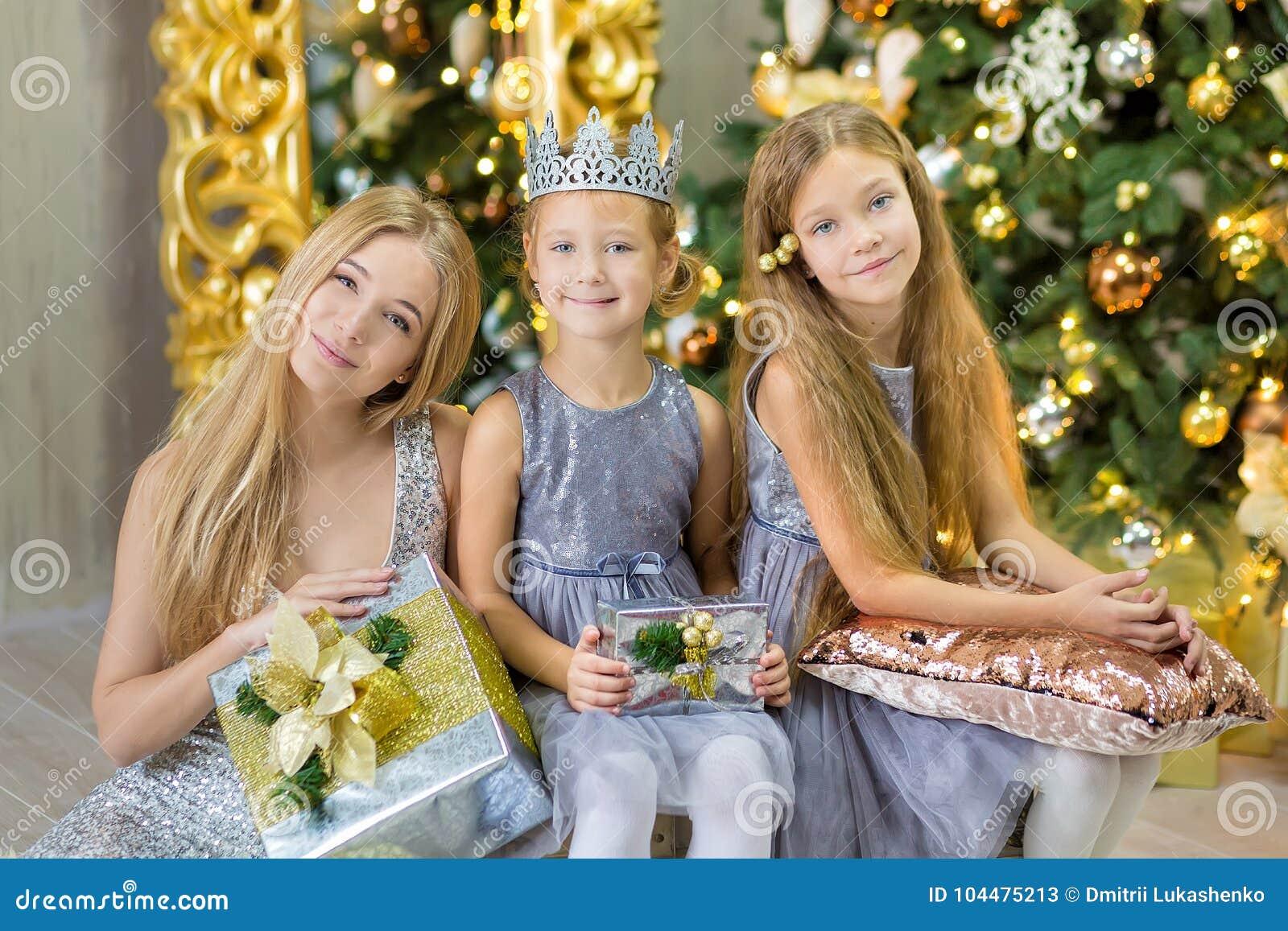 Frohe Weihnachten und frohe Feiertage nette kleines Kindermädchen, die zuhause den weißen grünen Weihnachtsbaum mit vielen Gesche