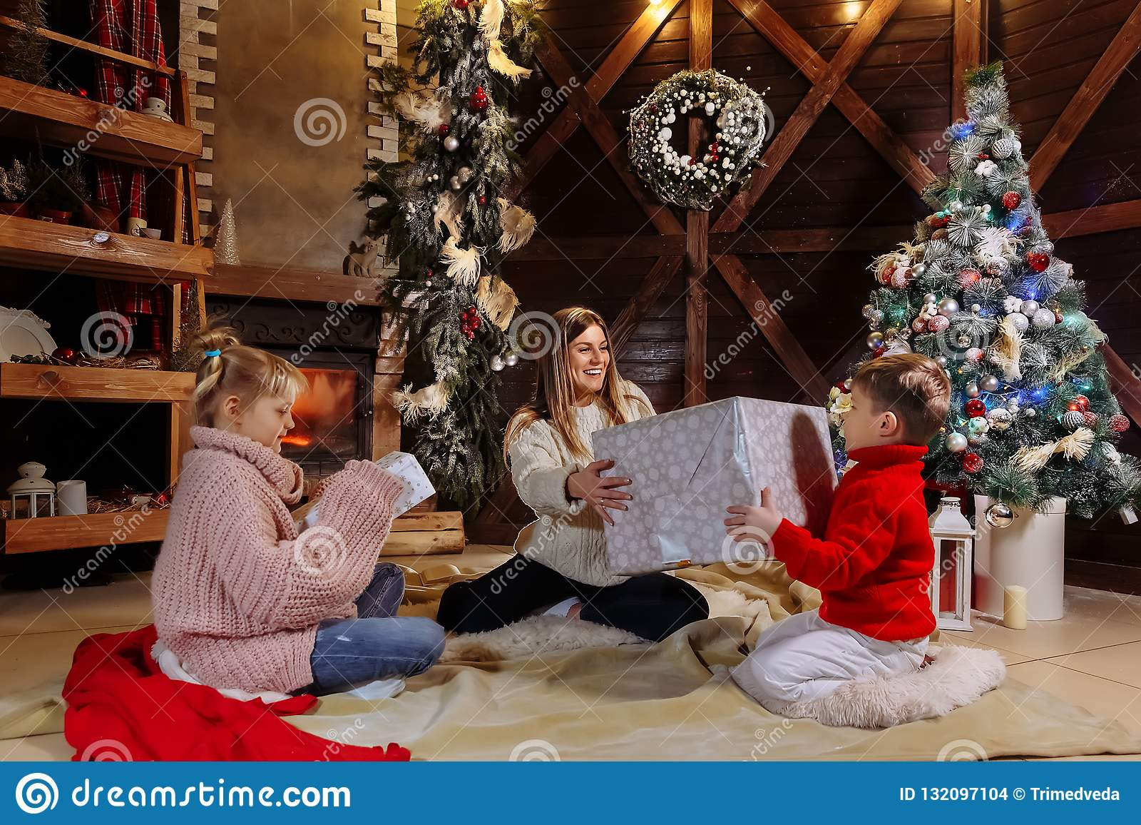Frohe Weihnachten und guten Rutsch ins Neue Jahr Nette Mutter und ihre nette Tochter und Sohn, die Geschenke austauschen Elternte