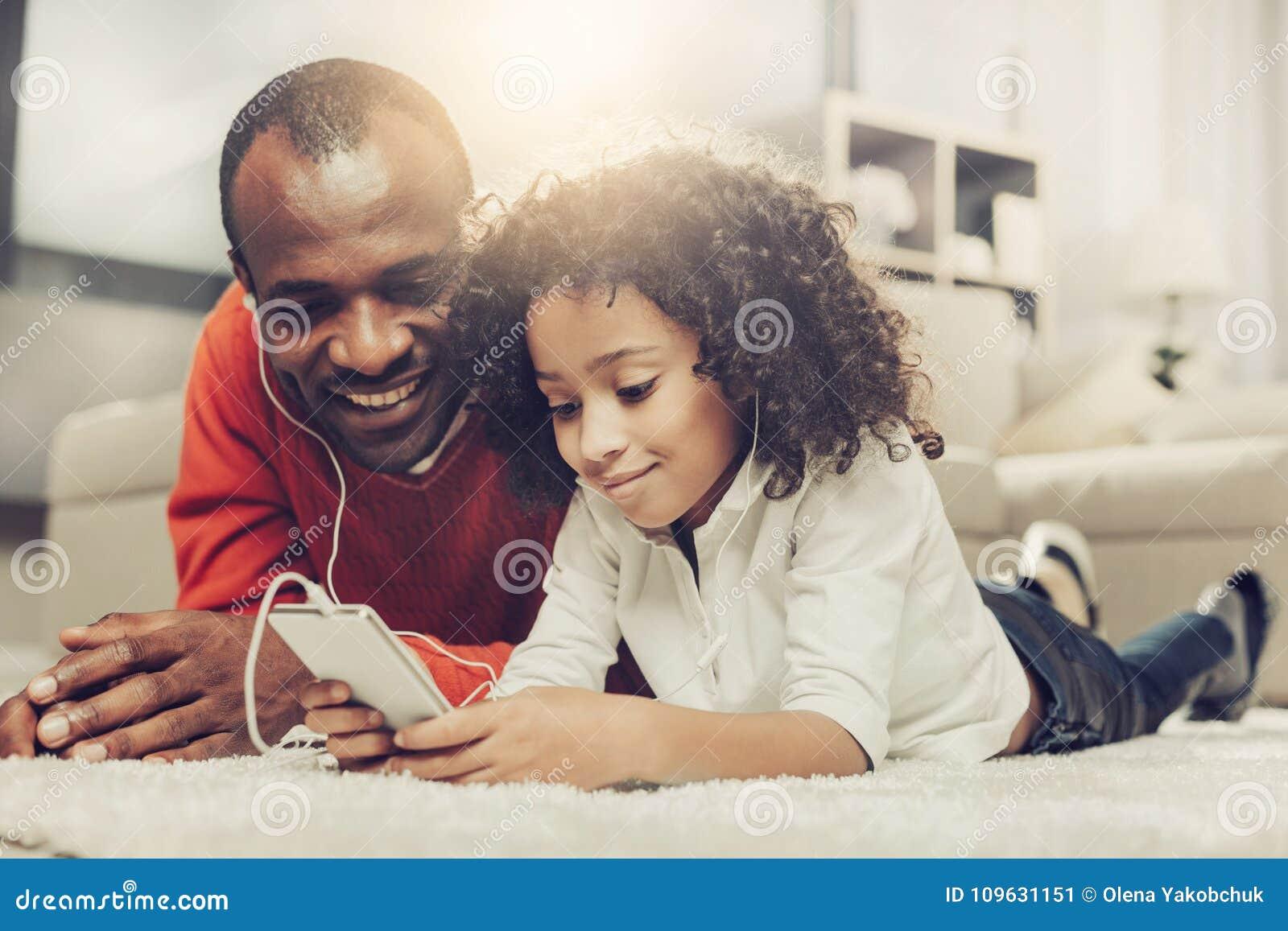 Froher Vater und Kind unter Verwendung des Handys mit Hörmuscheln