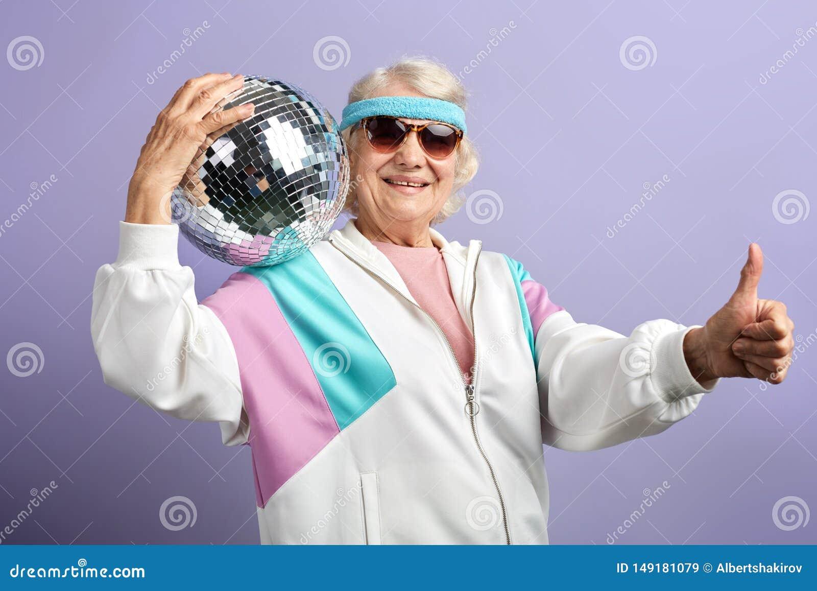 Frohes l?chelndes Greisinportr?t gekleidet in der Sportkleidung, mirrow Ball halten