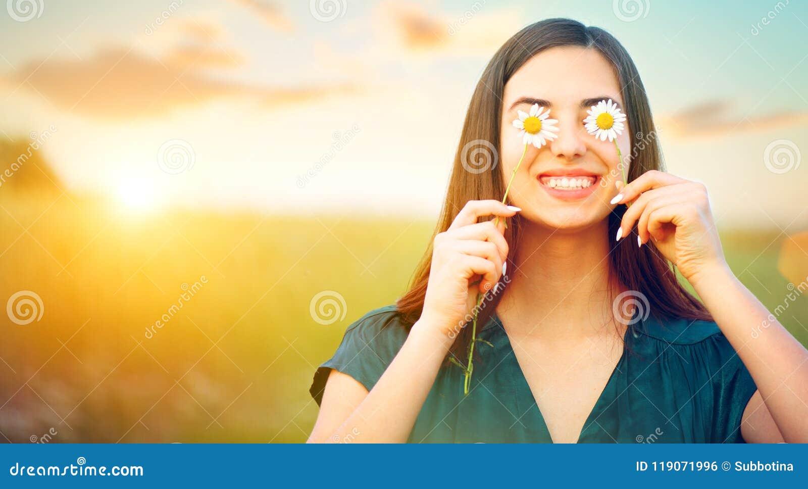Frohes Mädchen der Schönheit mit Gänseblümchenblumen auf ihren Augen Natur genießend und auf Sommerfeld lachend