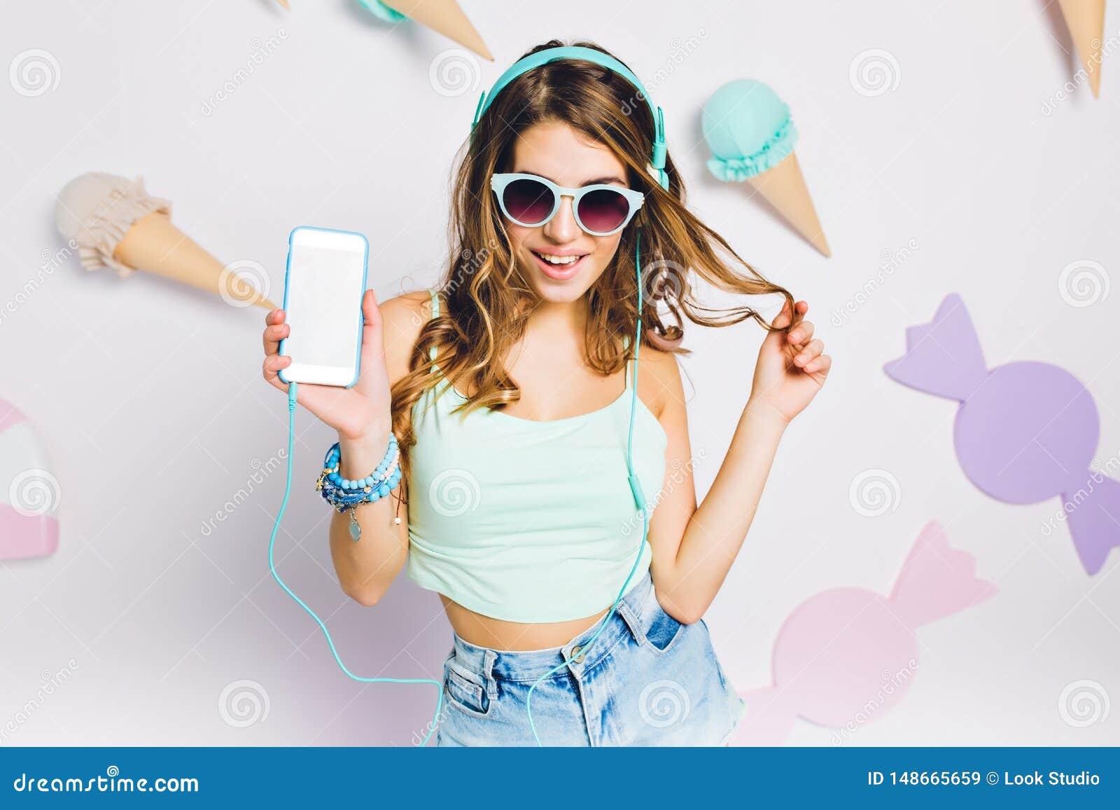 Frohes M?dchen in h?render Musik der blauen Zus?tze in ihrem Raum, Smartphone halten und spielen mit dem Haar Portrait von elegan