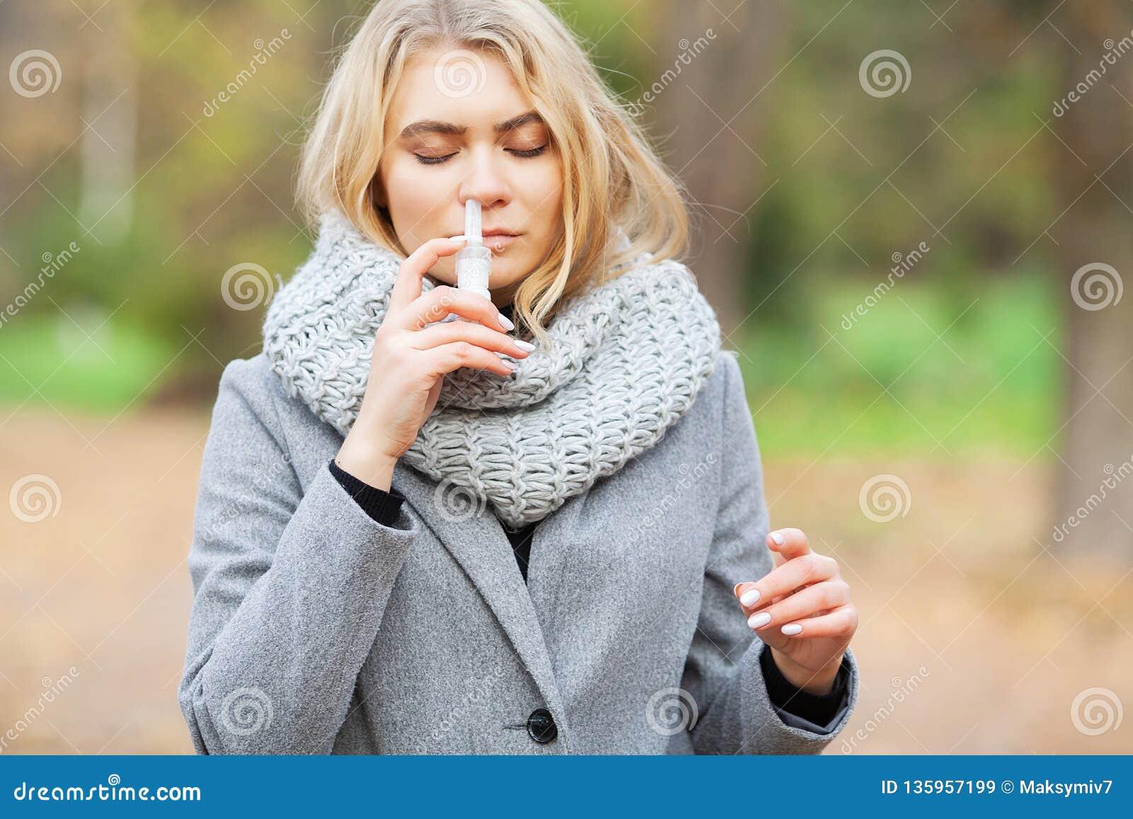 Froid et grippe La jeune femme malade emploie un pulvérisateur de nez à la rue dehors