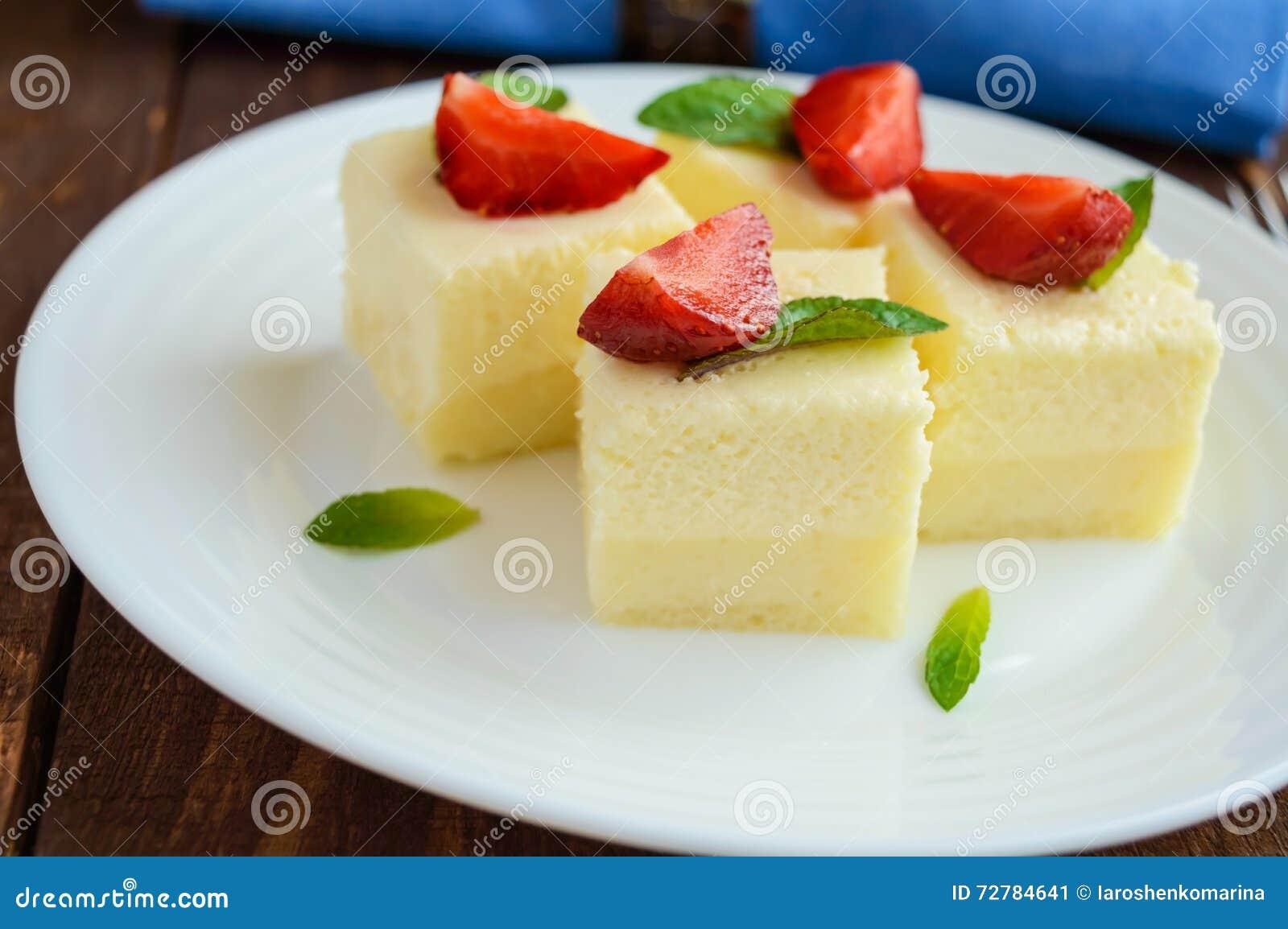 Fromage blanc sensible et soufflé crémeux sous forme de cubes, décorant des feuilles en bon état et des fraises fraîches