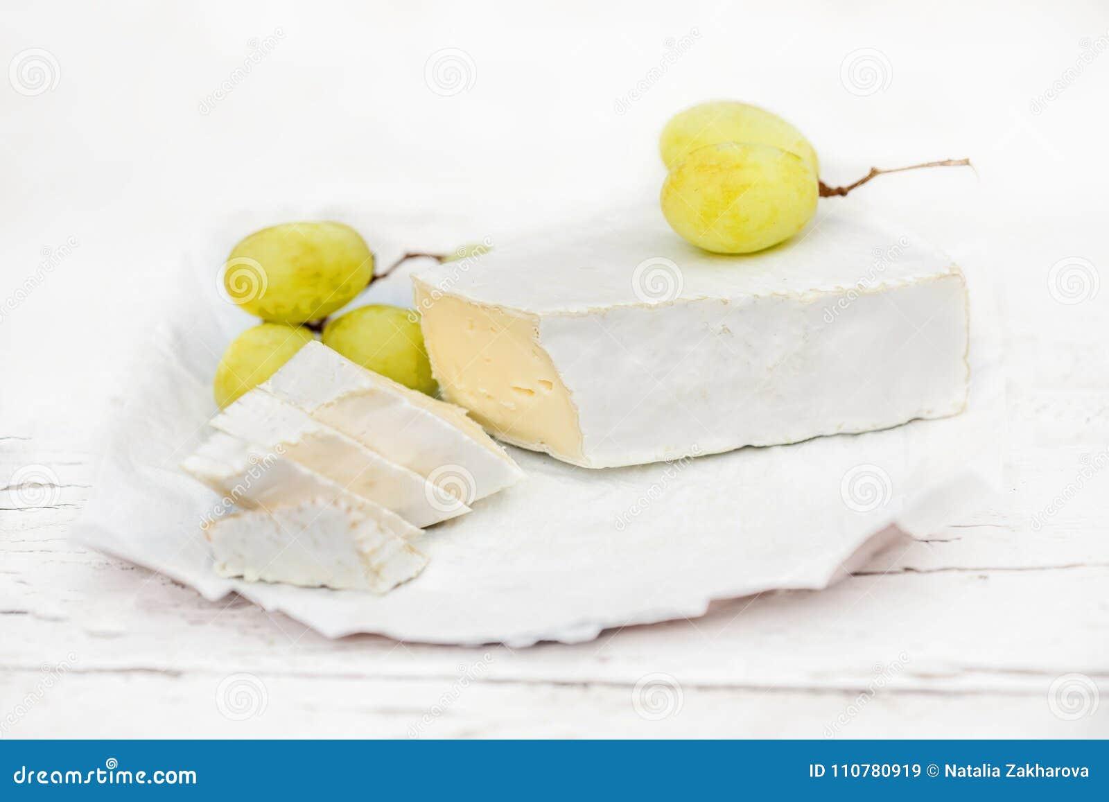 Fromage frais de brie avec des tranches et raisin sur rustique blanc sur un courtiser